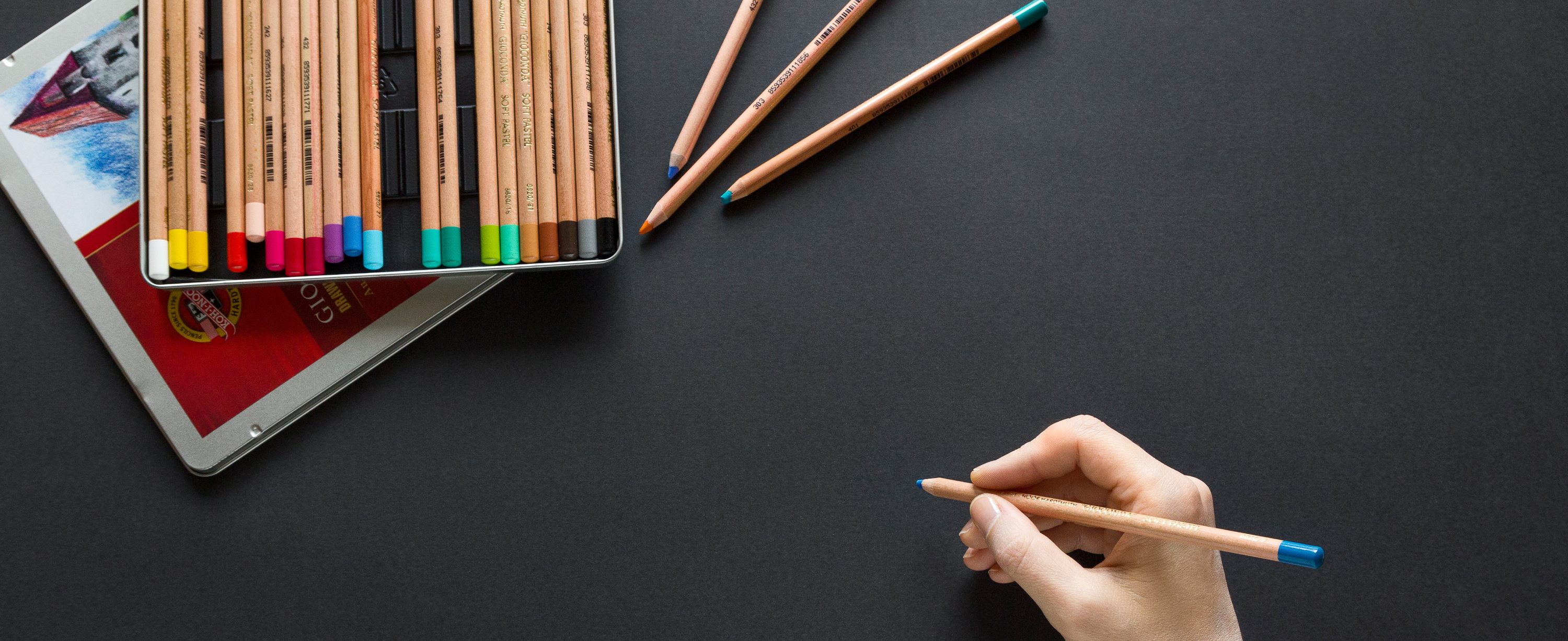 Person holding colored pencil. Photo by Neven Krcmarek on Unsplash.