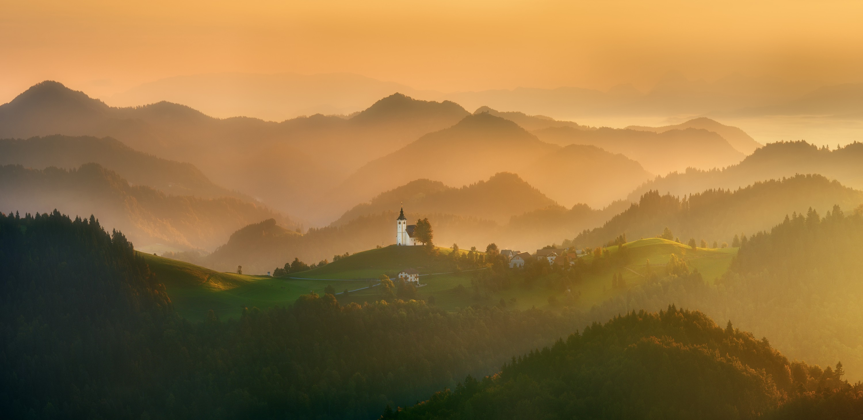 A fine art photograph of a small church which appears backed by golden, yellow light in rolling green hills