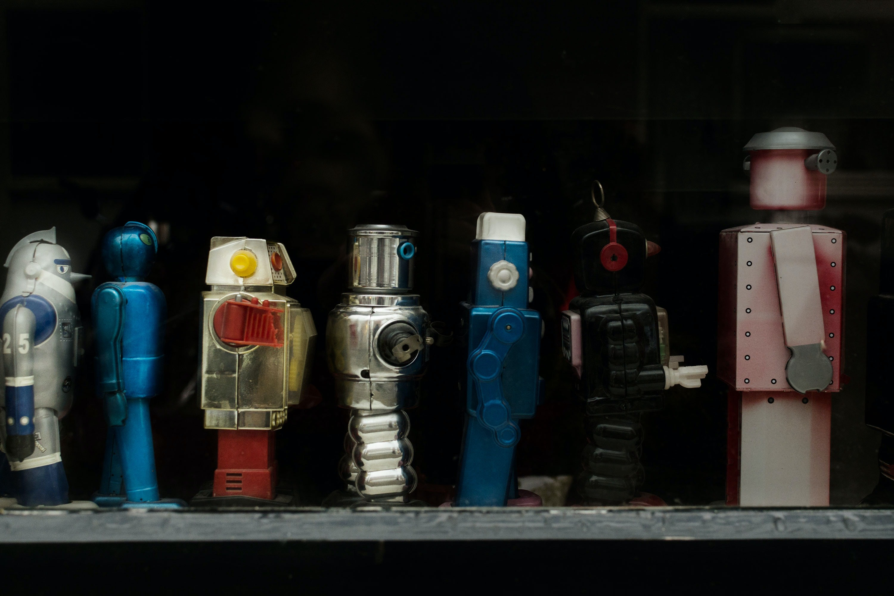 A variety of toy robots stand on a shelf.