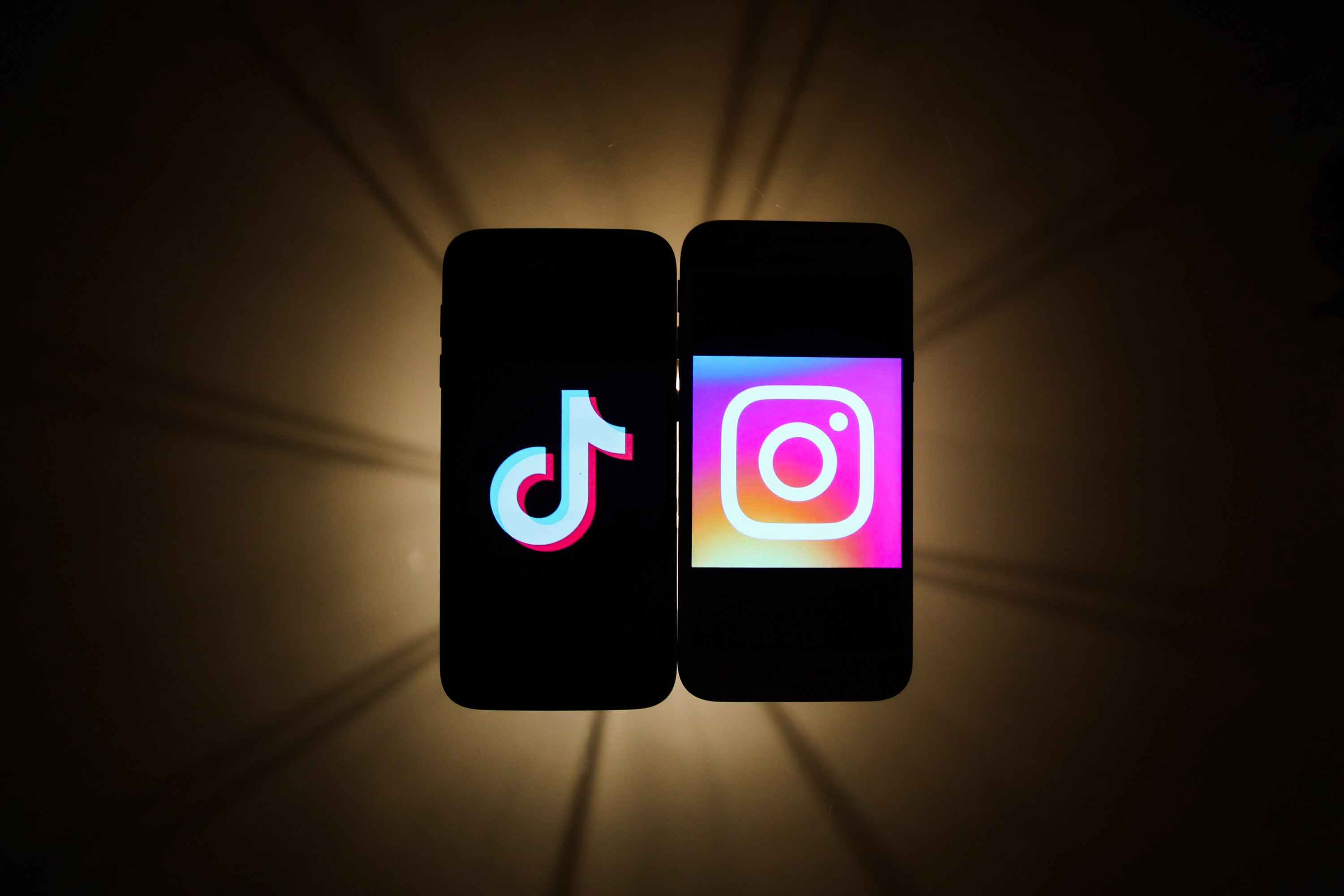 TikTok and Instagram logos are seen displayed on a phone screens in this photo illustration.