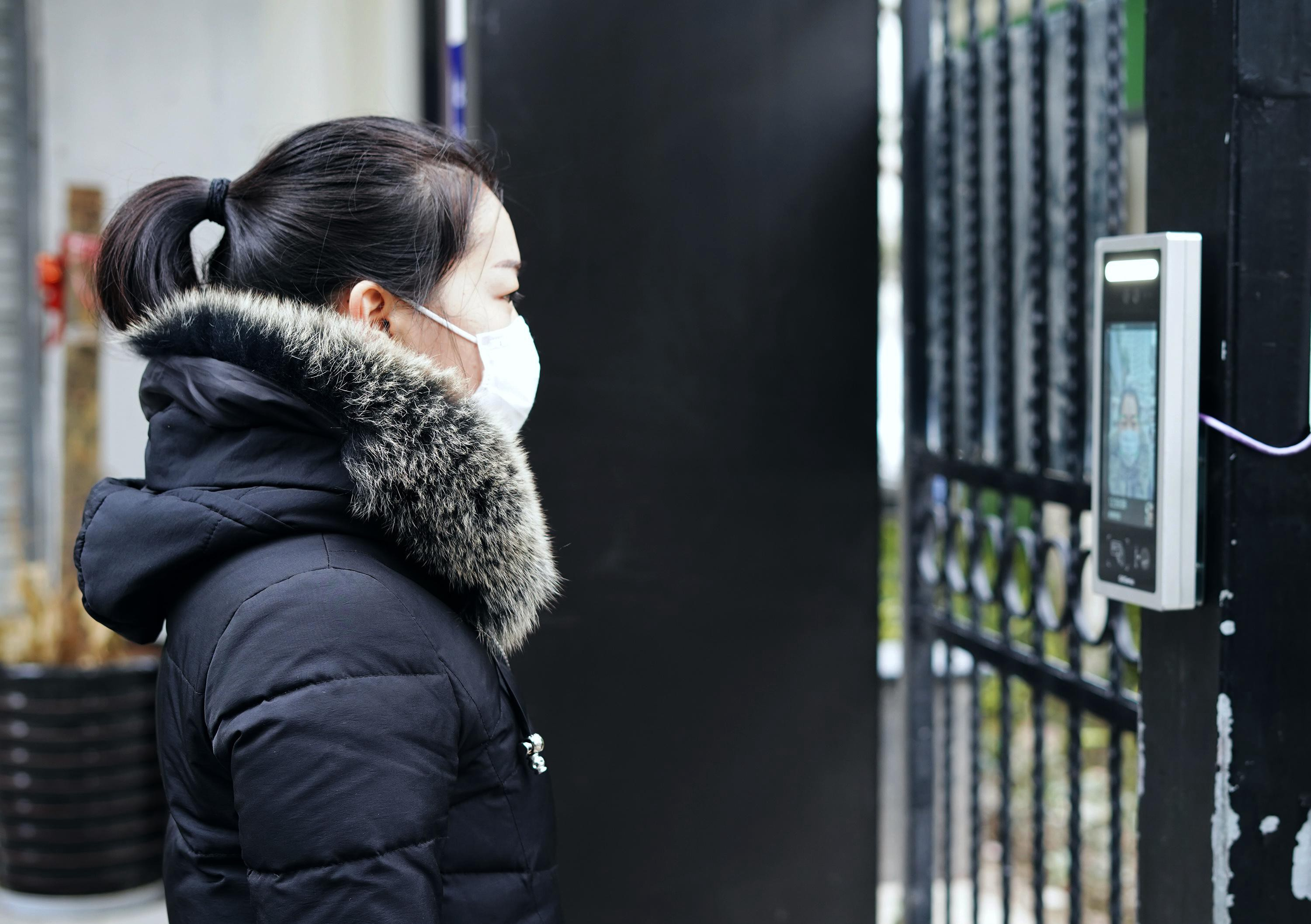 A woman with a face mask uses a facial recognition system to enter a residence.