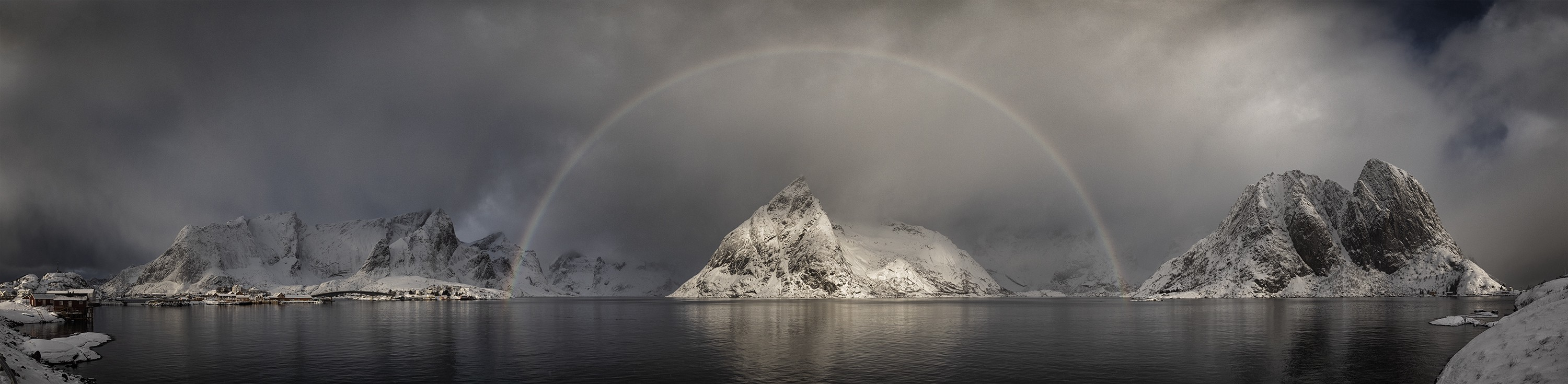 A gray, nearly black and white looking scene of dark water and snow-capped dark mountains is visited by a thin, pale rainbow