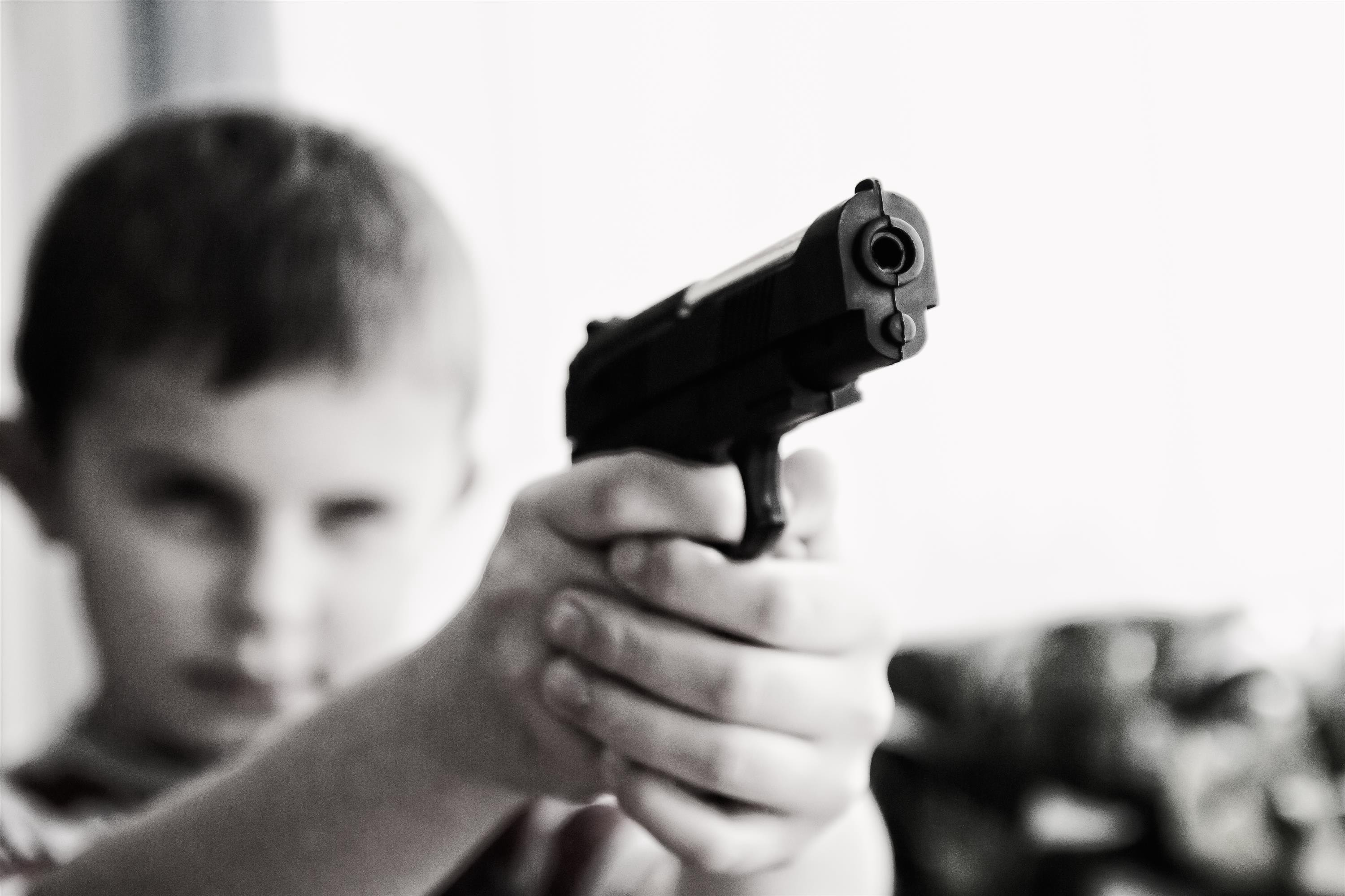 Child aims pistol toward the camera. His expression is determined.