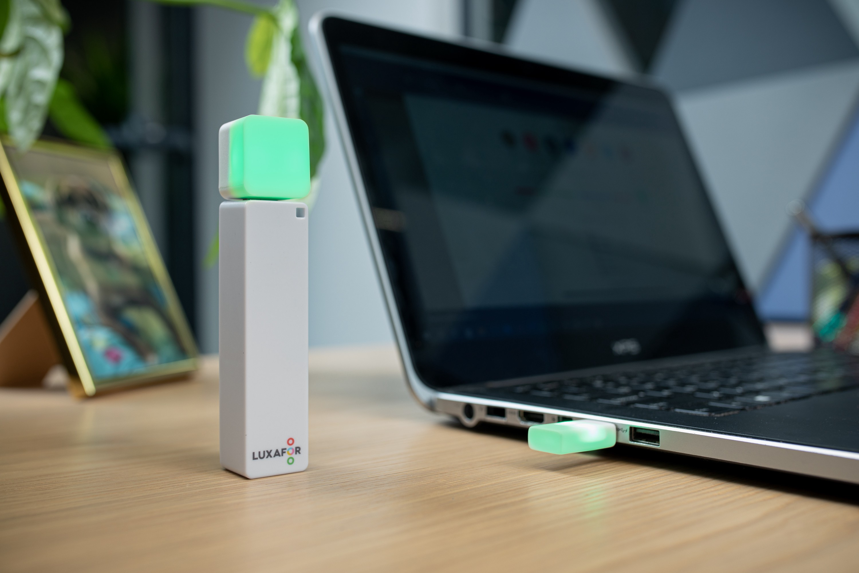 The Luxafor Bluetooth on a light colored desk. The device is connected to a laptop computer and it showing a green light.