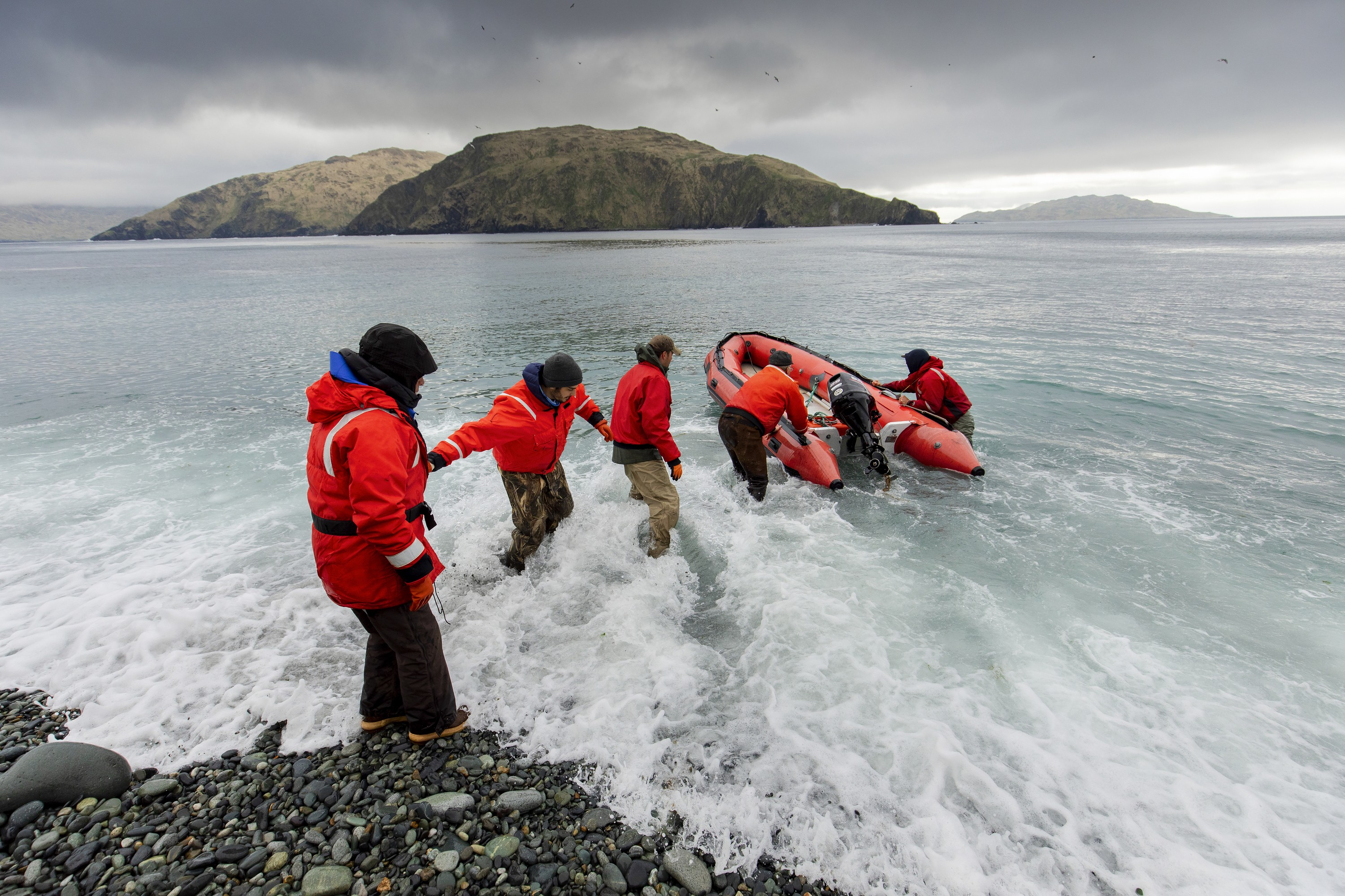 Action photo of a chain of people in bright orange survival float jackets turning an inflatable skiff back into the ocean from a rocky shore.