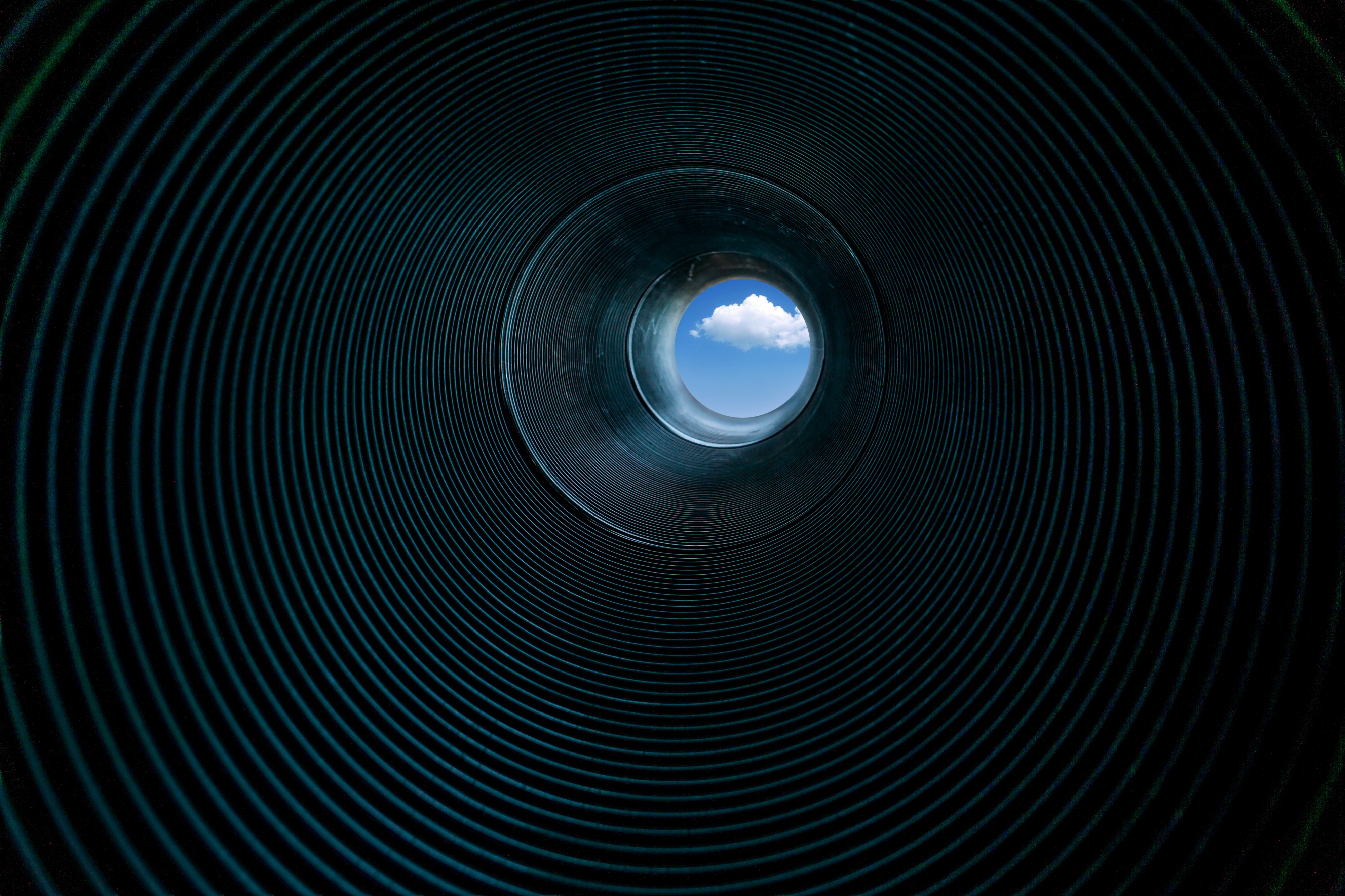 A spiral tube showing light at the end of the tunnel
