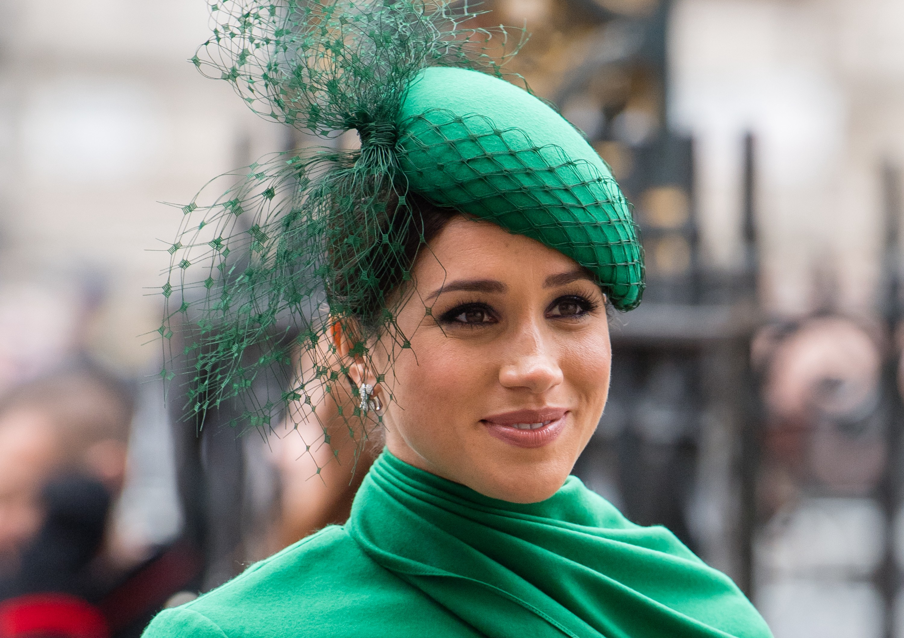 Meghan, Duchess of Sussex, at a public event wearing a green outfit with matching hat.