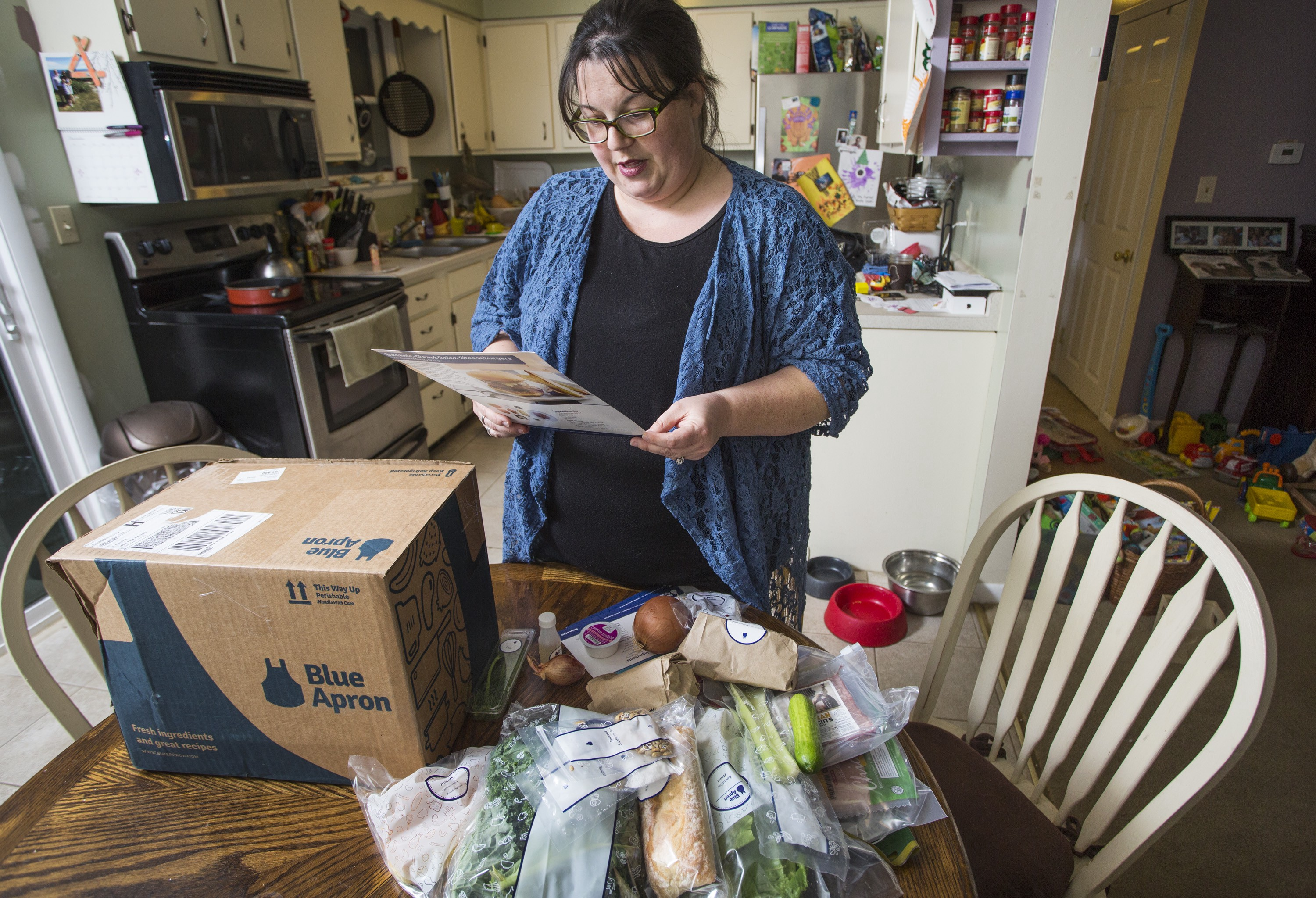 Emily Griffin reads a recipe for a Blue Apron meal while unpacking her box at her Lisbon Falls home.