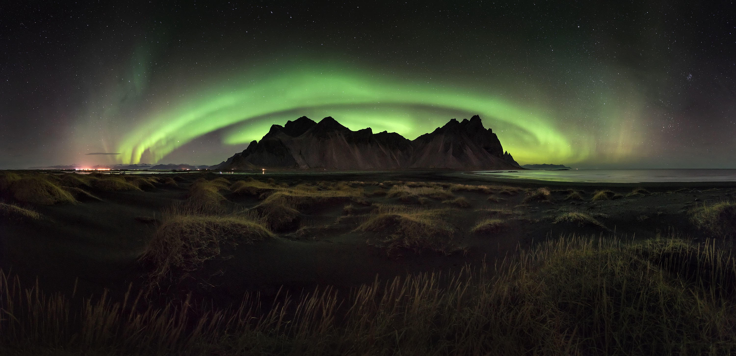 "A craggy range surrounded by a ""halo"" of green glowing northern lights in the sky"
