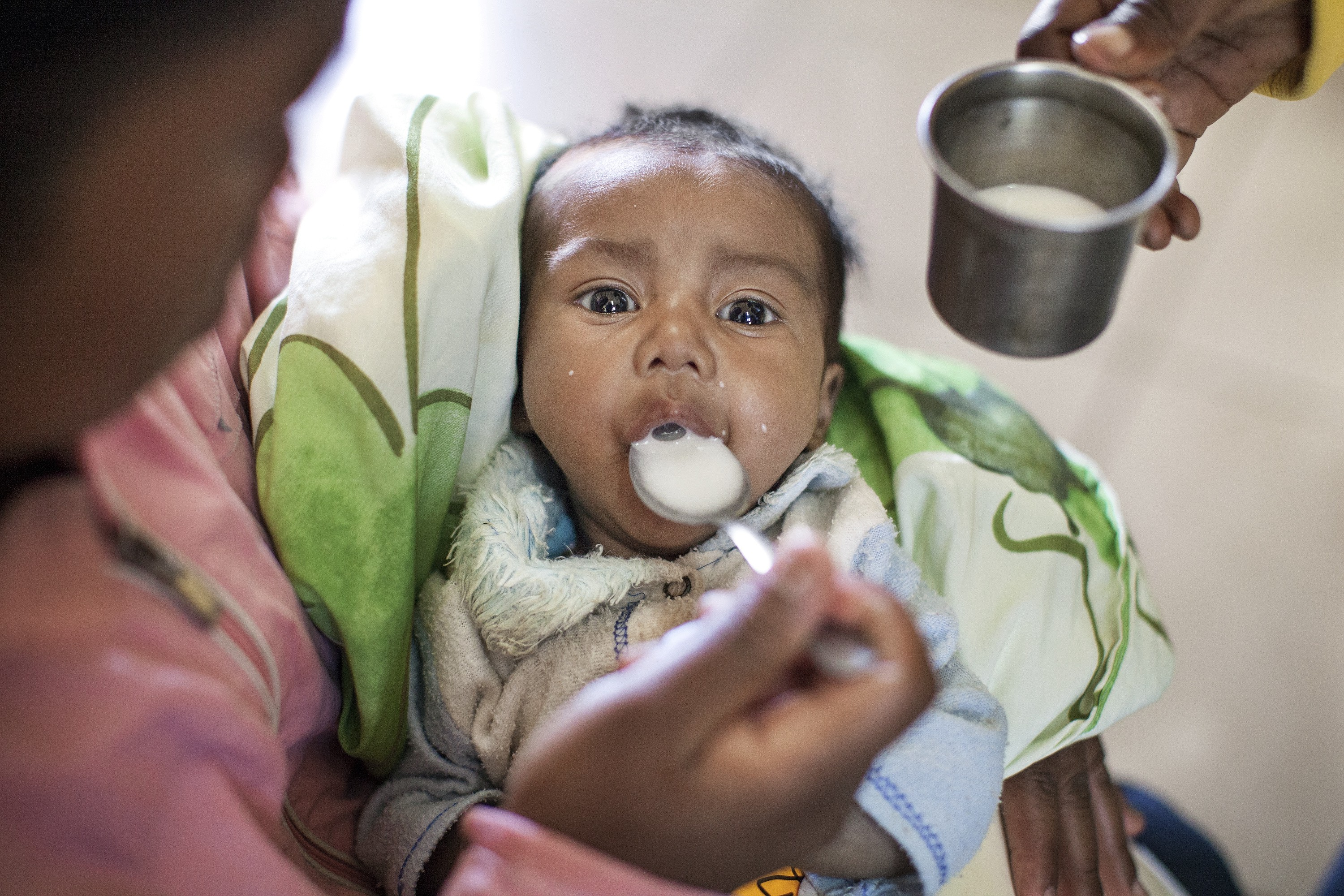 A mother in Madagascar feeds her child formula with a spoon.