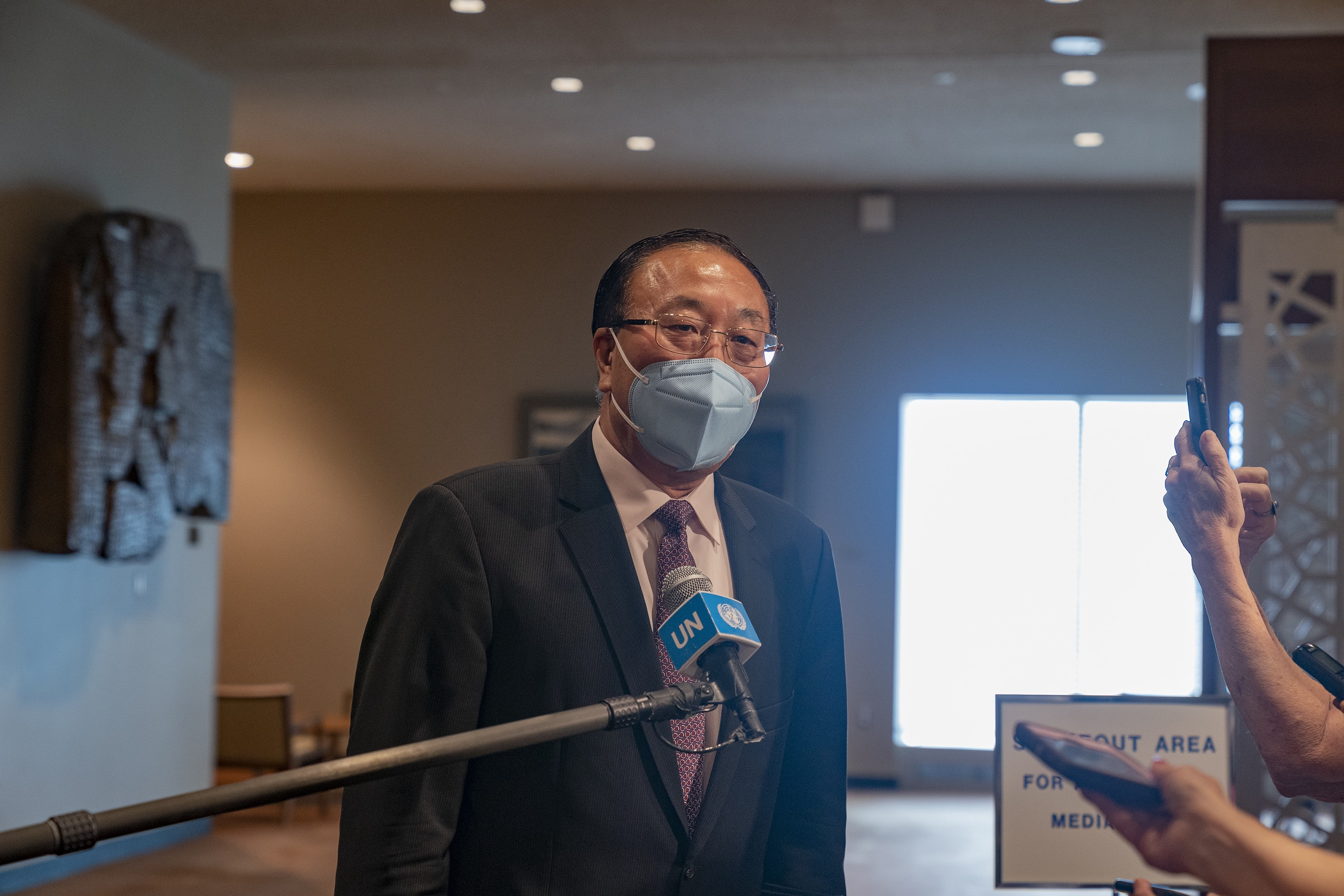 China's Permanent Representative to the UN Ambassador Zhang Jun talks to the press in a large room while wearing a blue face mask.