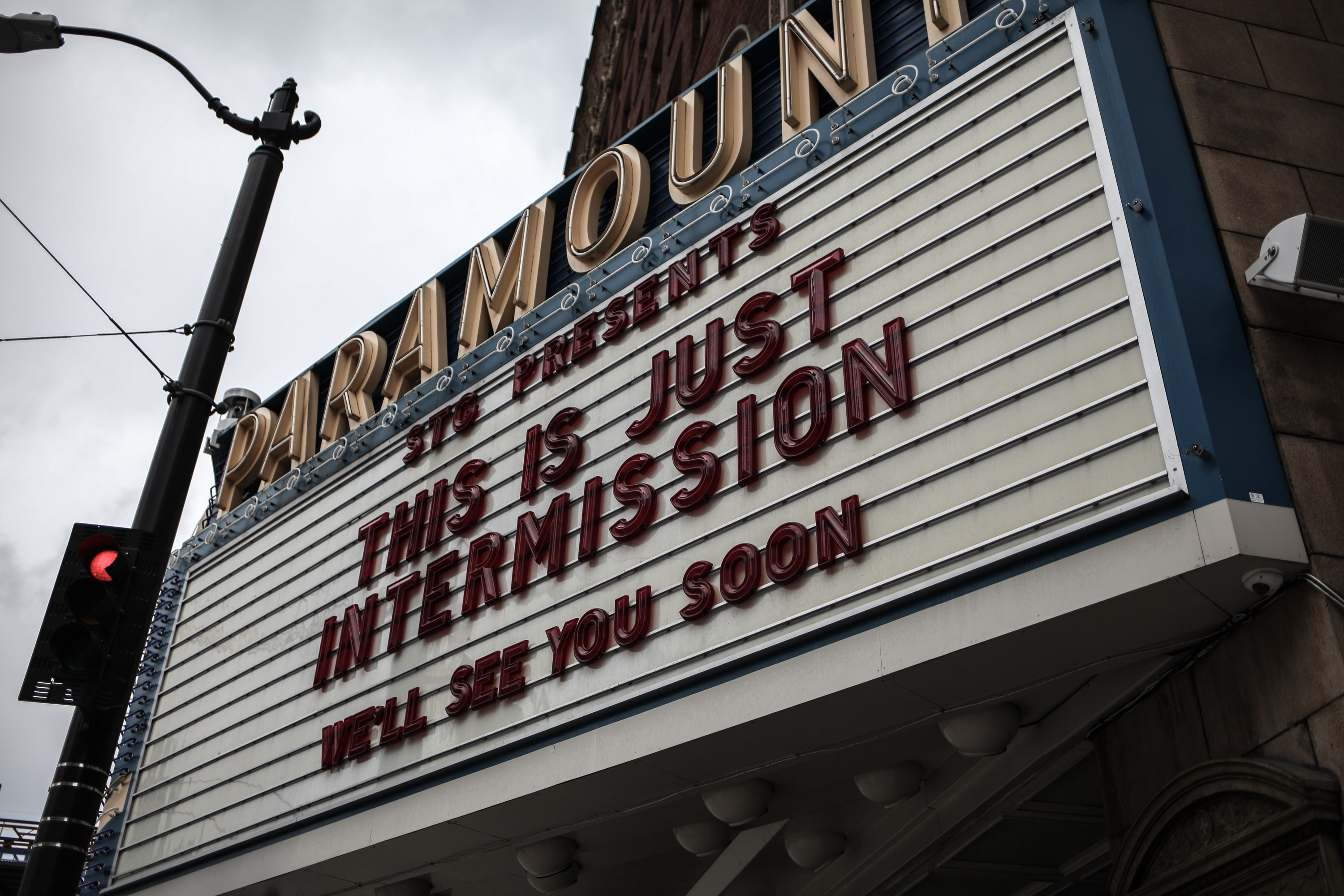 "A cinema billboard, with the letters spelling out ""STG presents THIS IS JUST INTERMISSION — We'll see you soon"