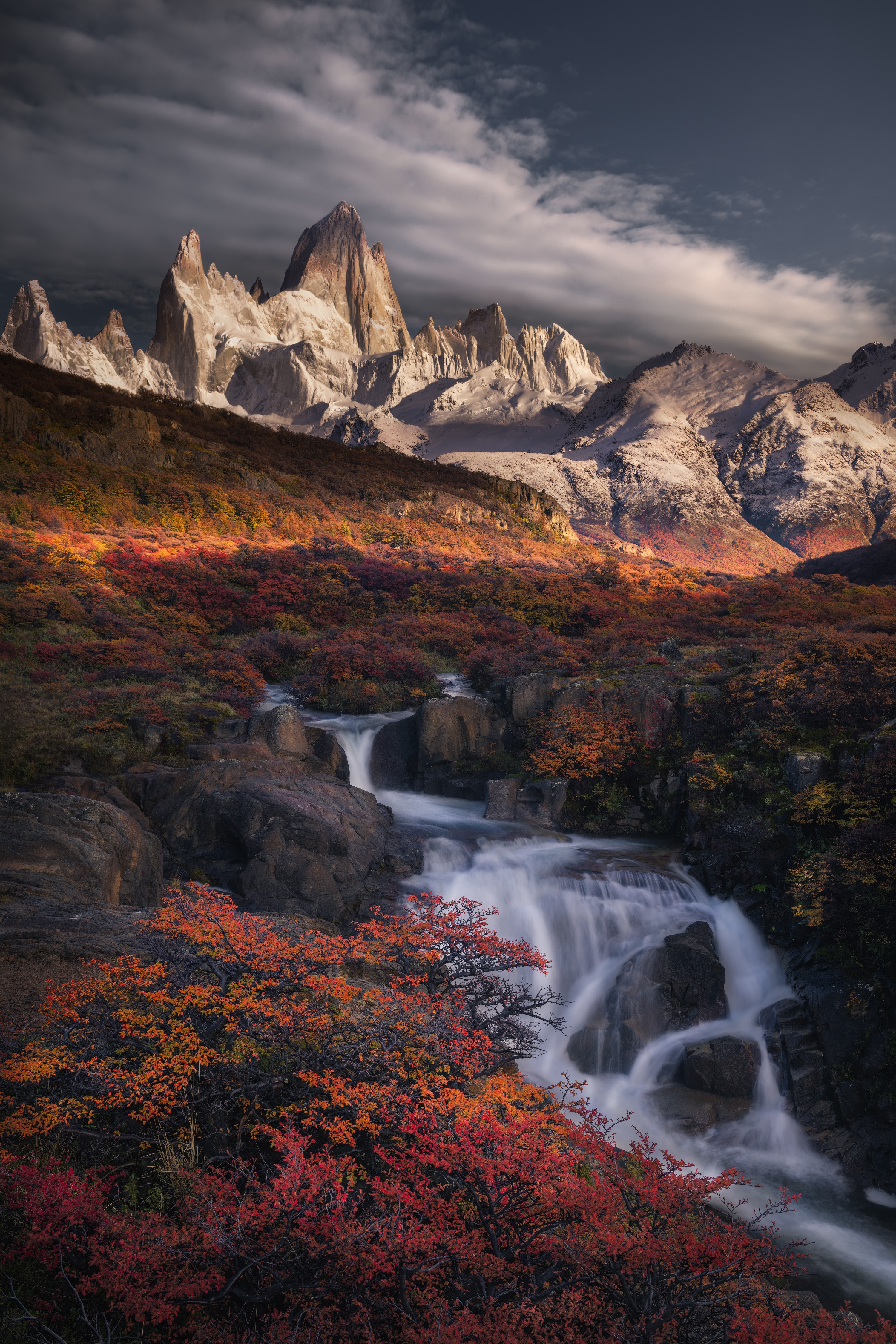 A photograph of a creek and waterfalls running downhill among fall leaves, with a mountain range in the background