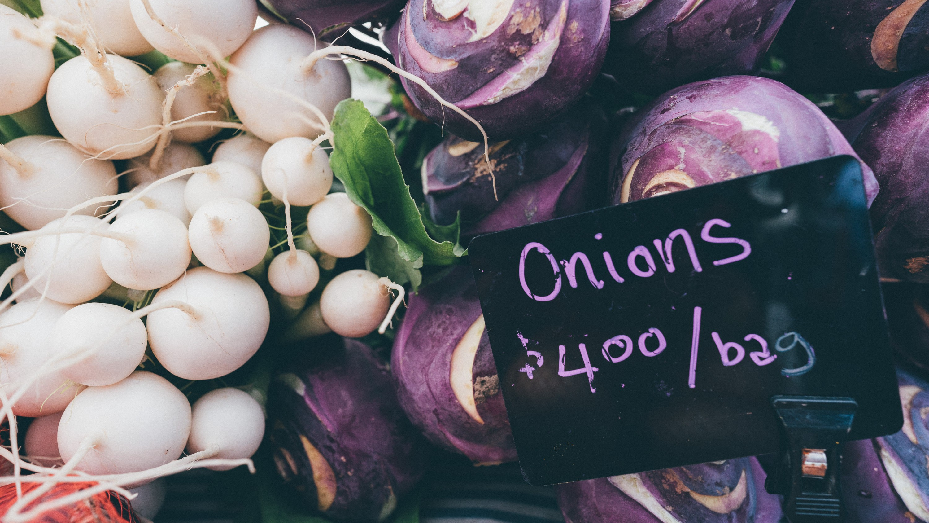 """Onions next sign saying """"Onions,"""" and a price on the sign."""
