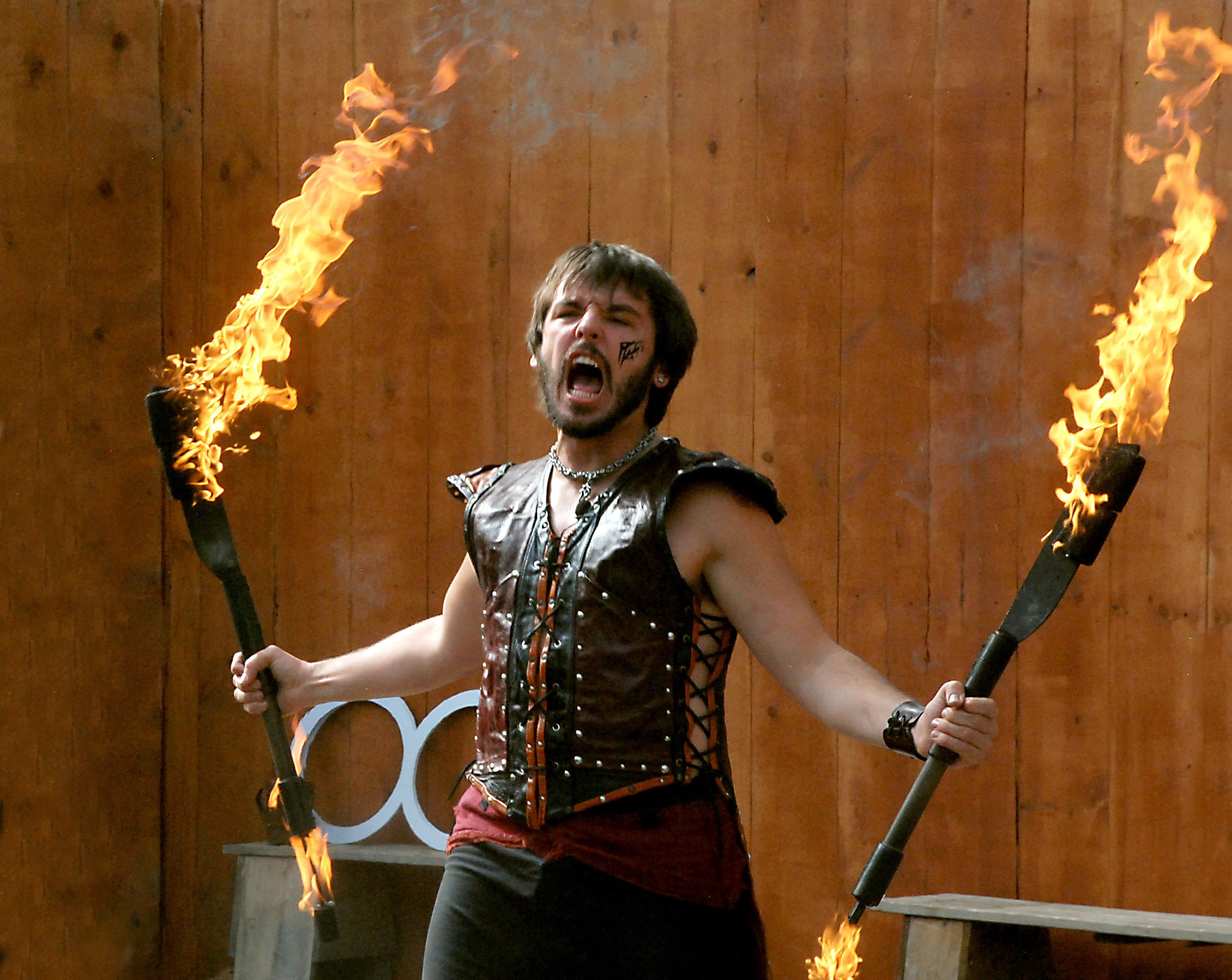 Angry young man in a medieval-looking tight-fitting vest holding two burning torches and yelling