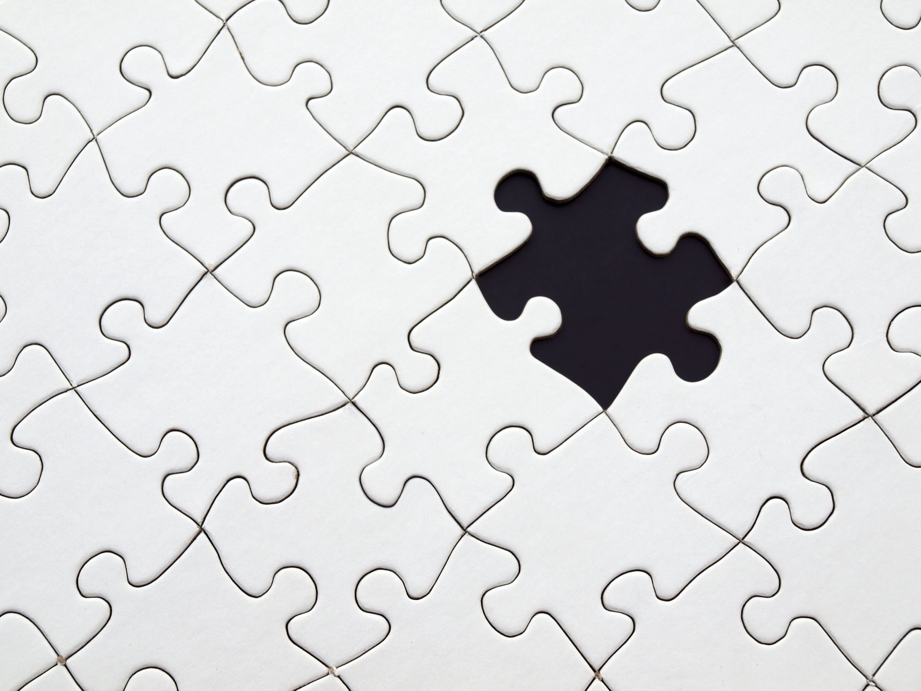 A photo of an all-white jigsaw puzzle with one piece missing, revealing a black background.