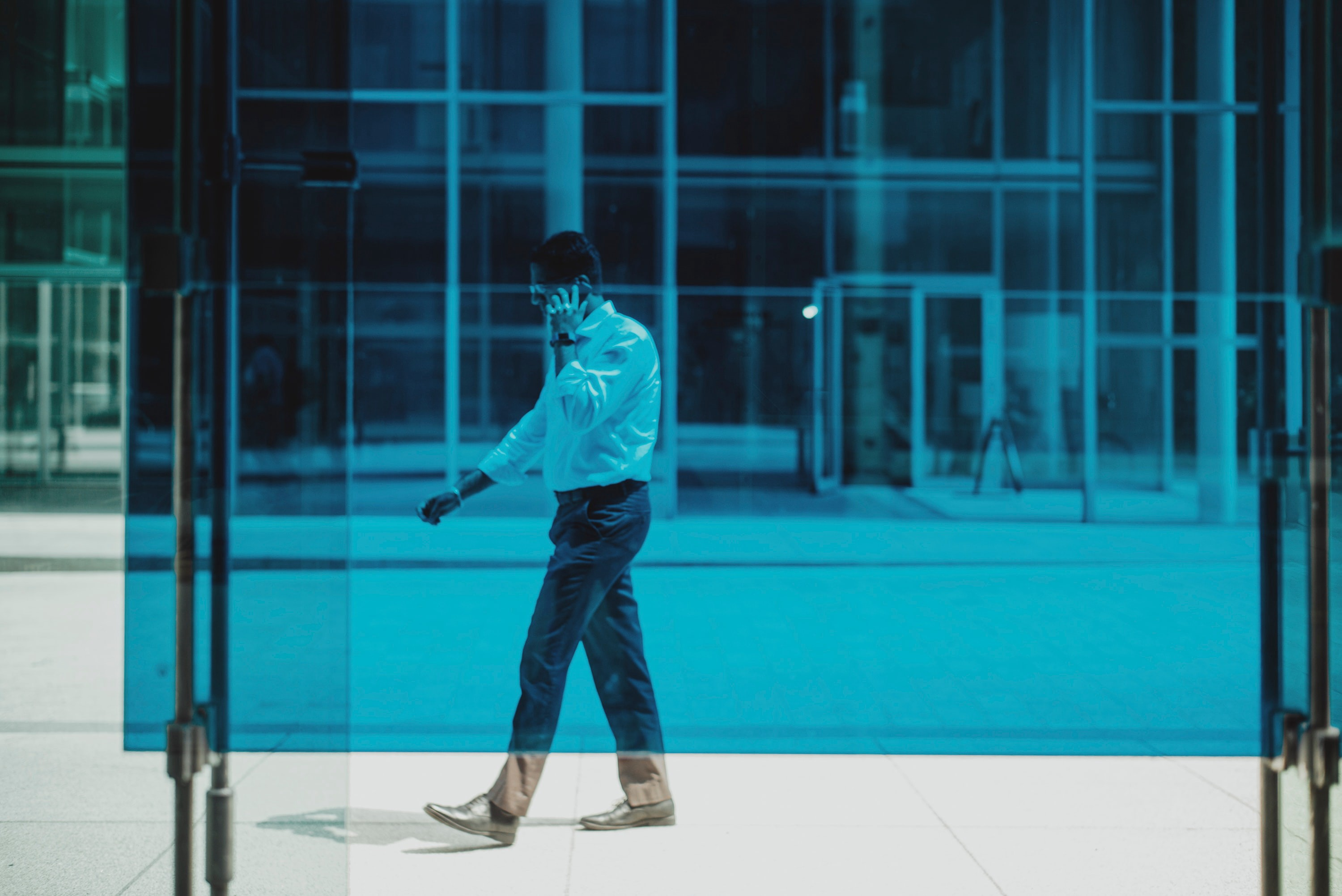 A man with a phone walking behind a blue glass.