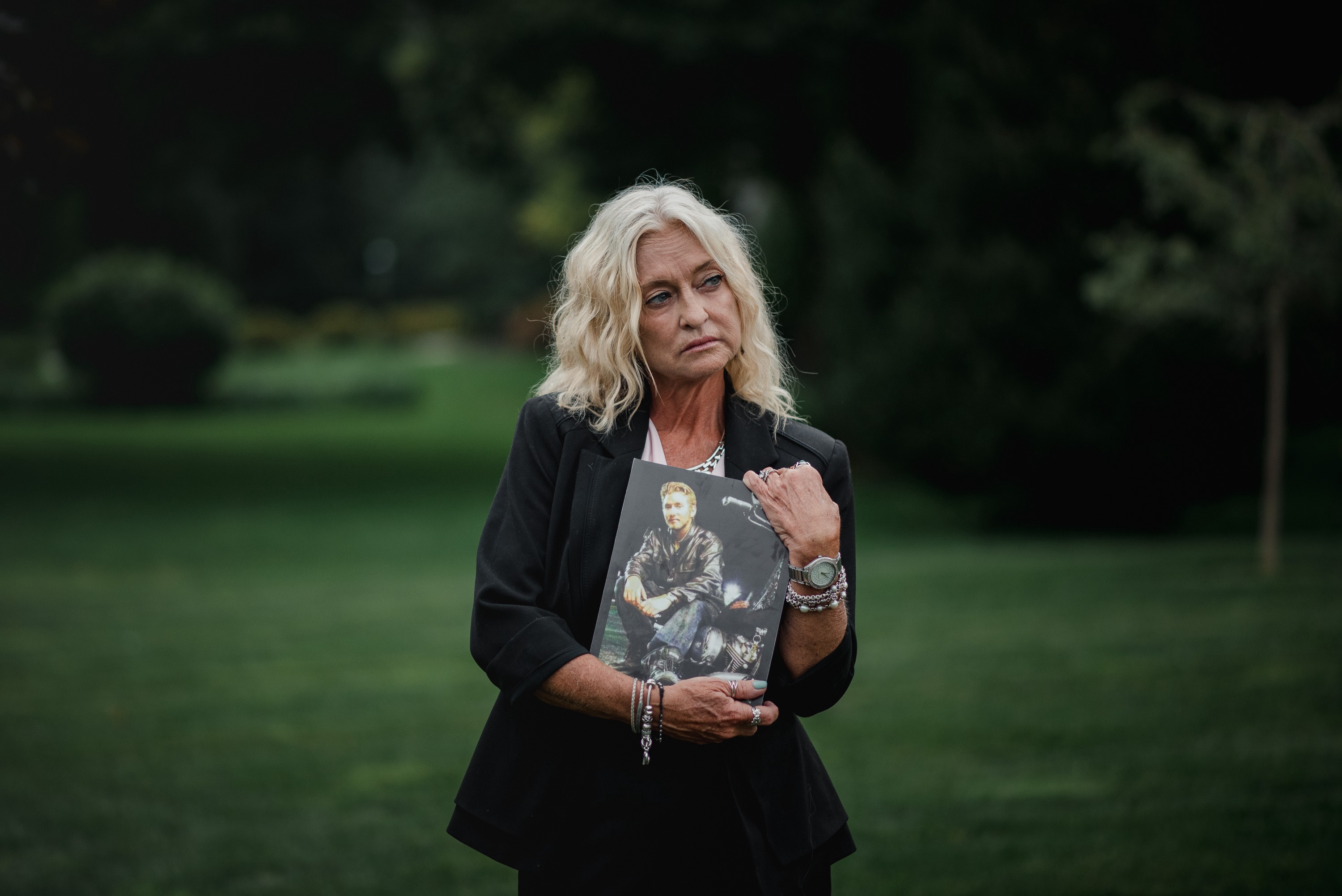 Mary Kief stands for a portrait while holding an old photo of her son, Benjamin