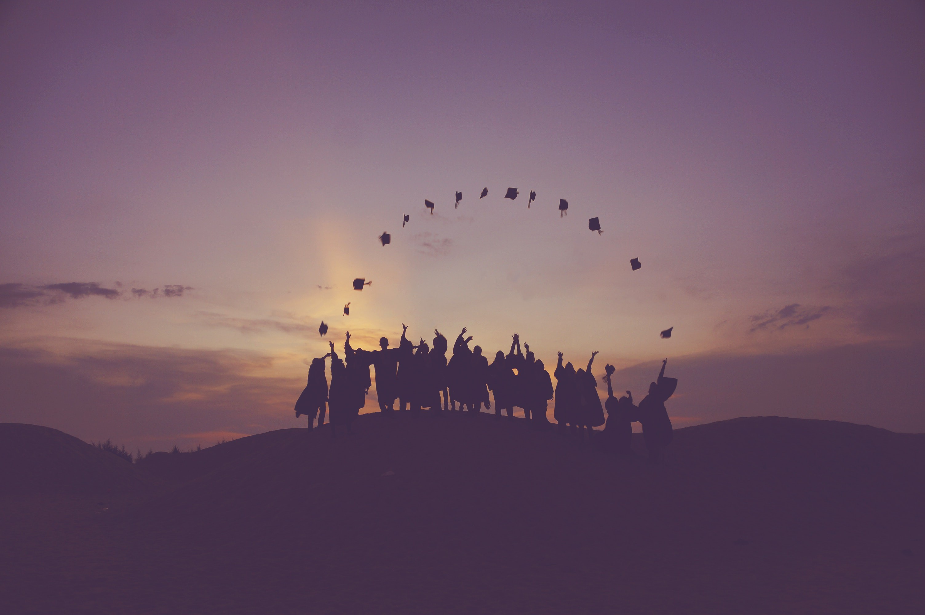 A group of graduates in silhouette throw their graduation caps in the air.