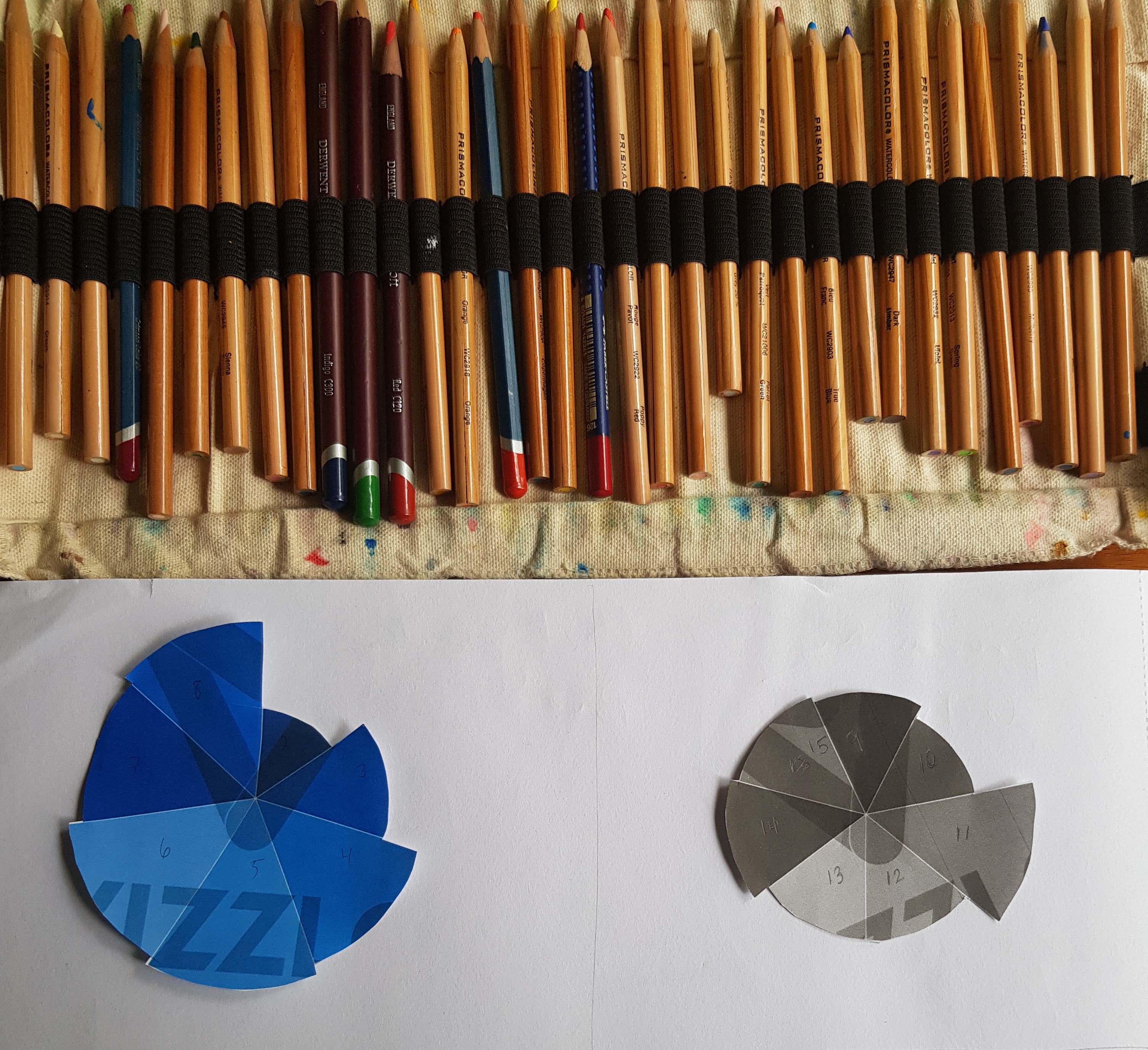 Color pencils, neatly lined up, with rose charts made of folded paper