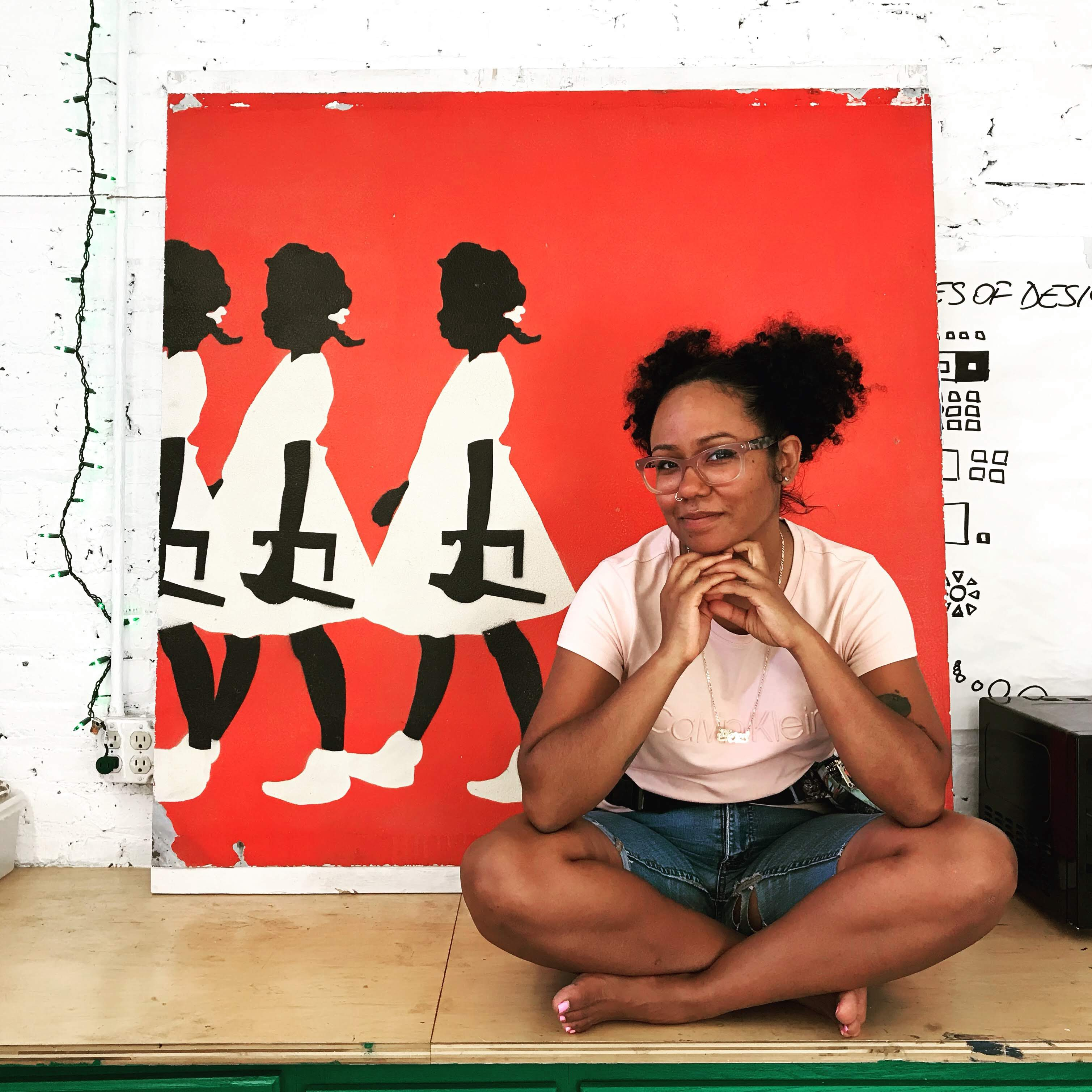 A smiling woman sits on the floor in front of a bright painting featuring three Black girls. Sharon has black hair & glasses