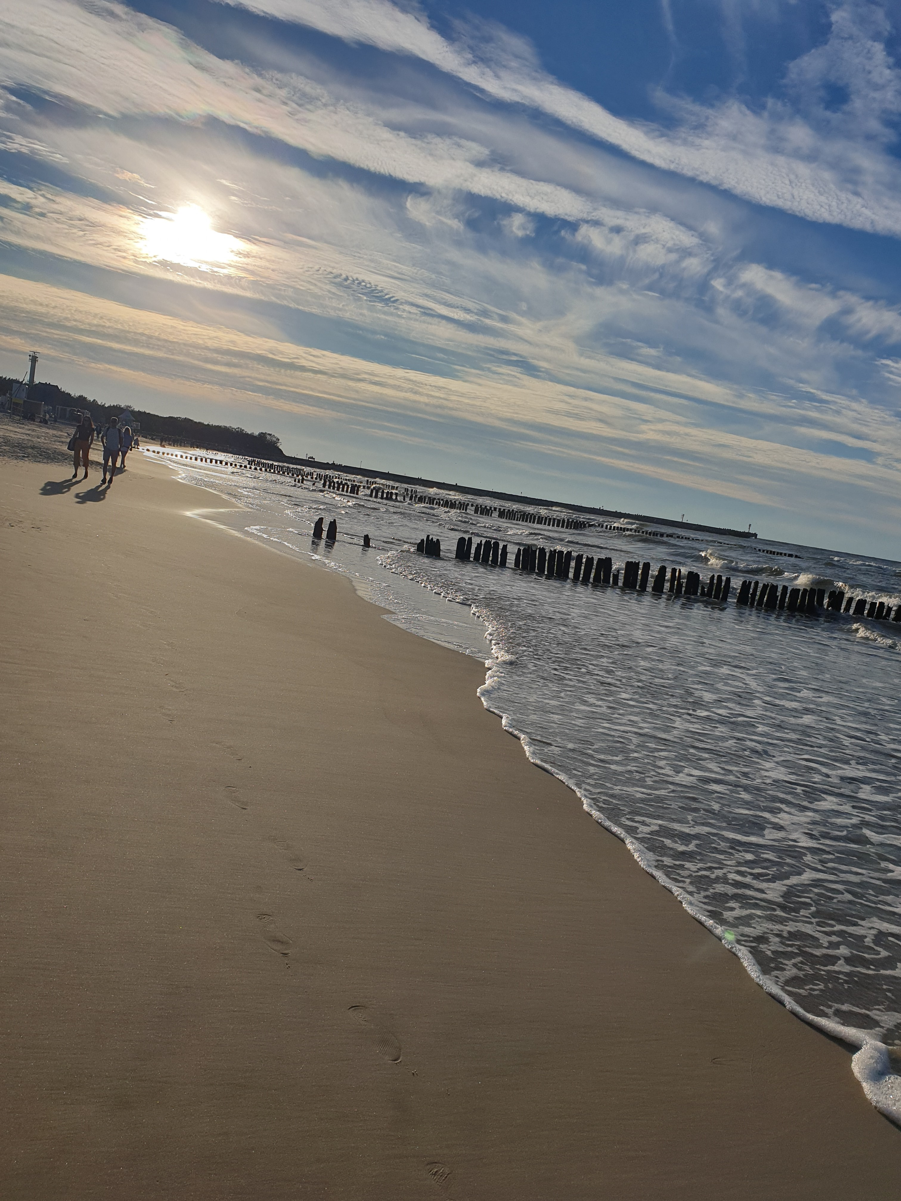 A picture I took of the gentle waves caressing the smooth sand as the sun starts to set in the evening, behind fluffy clouds