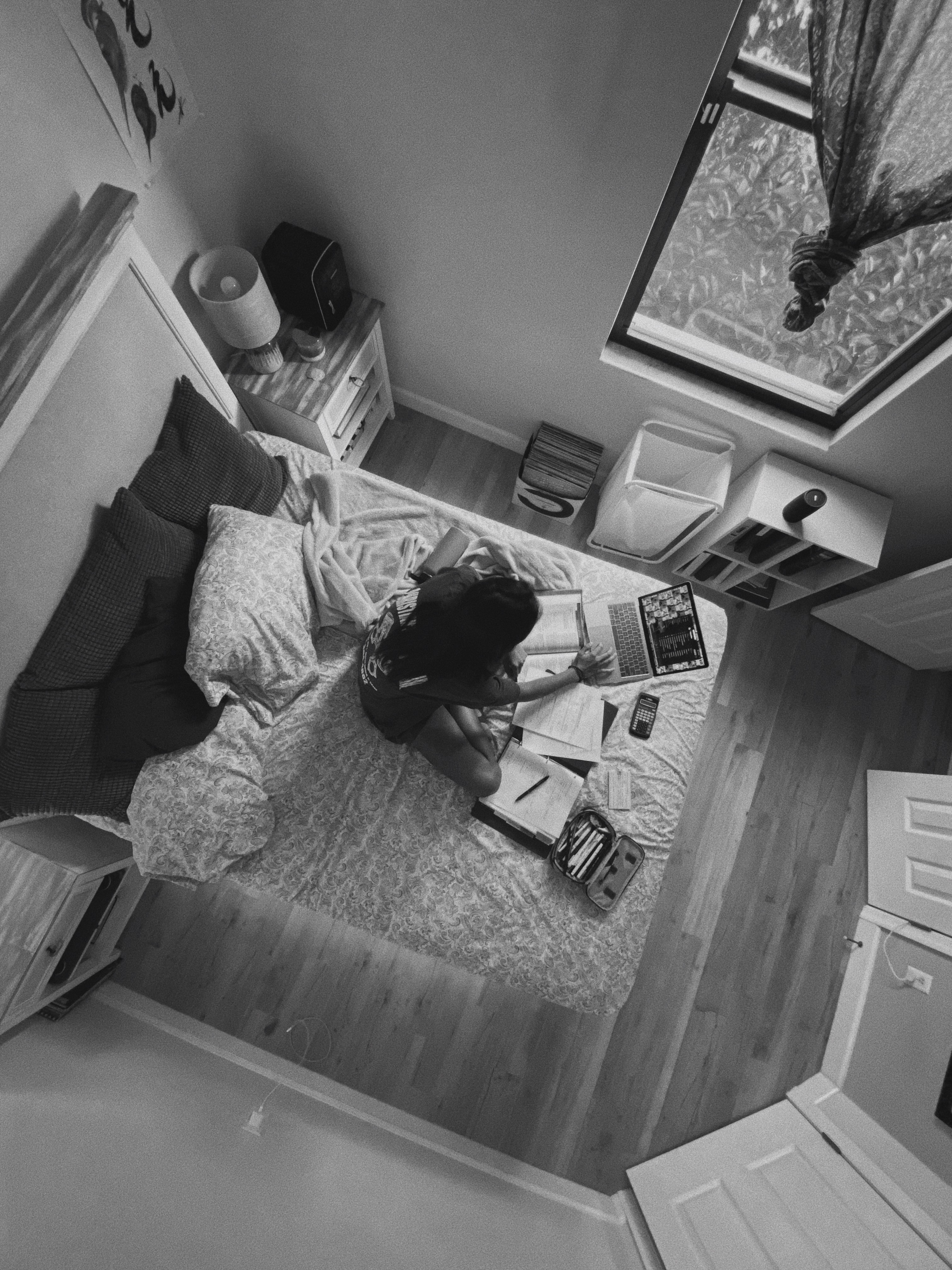 A woman sits alone in her bedroom typing on her computer.)