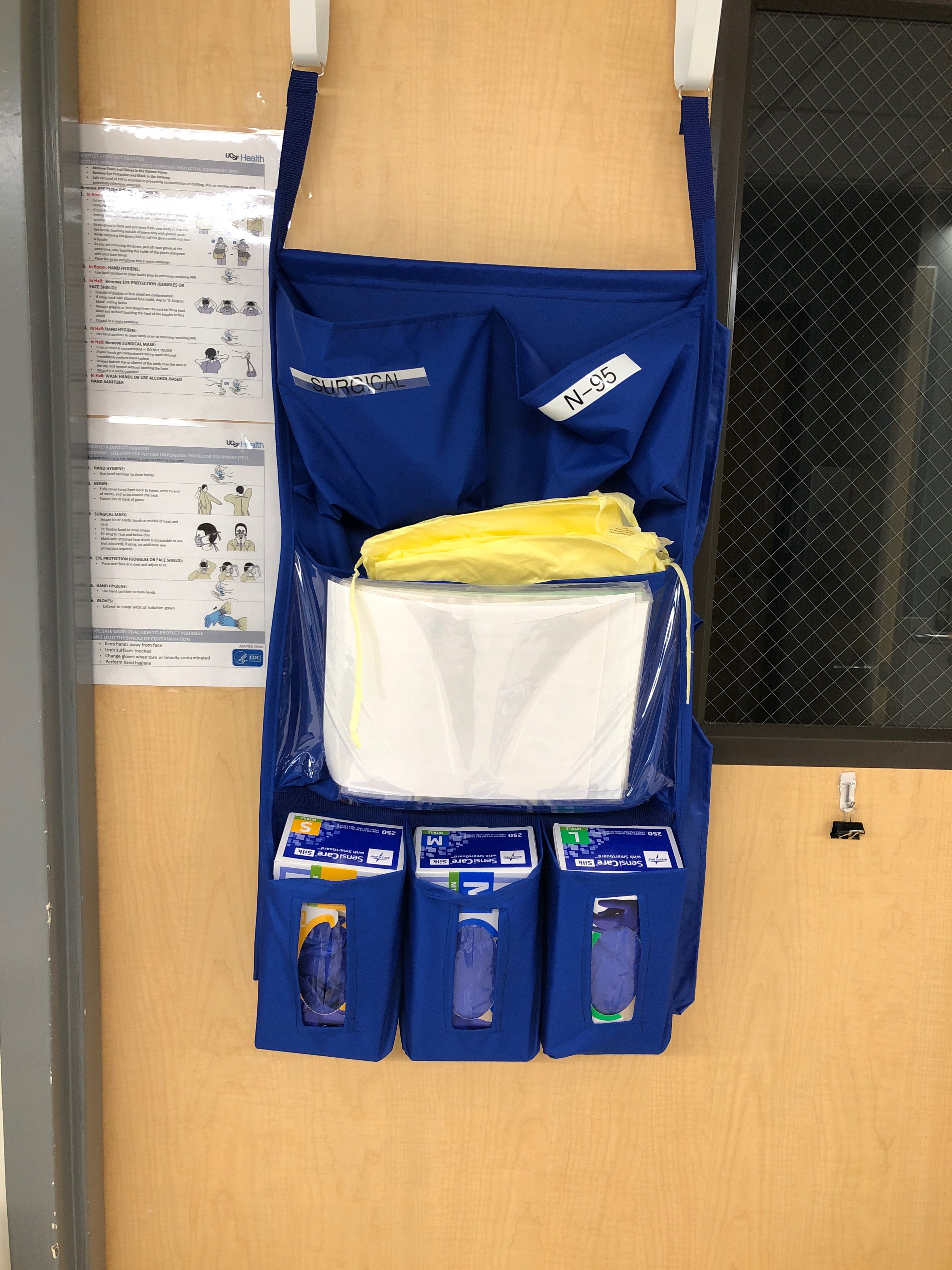 Personal protective equipment hanging outside of a patient's room