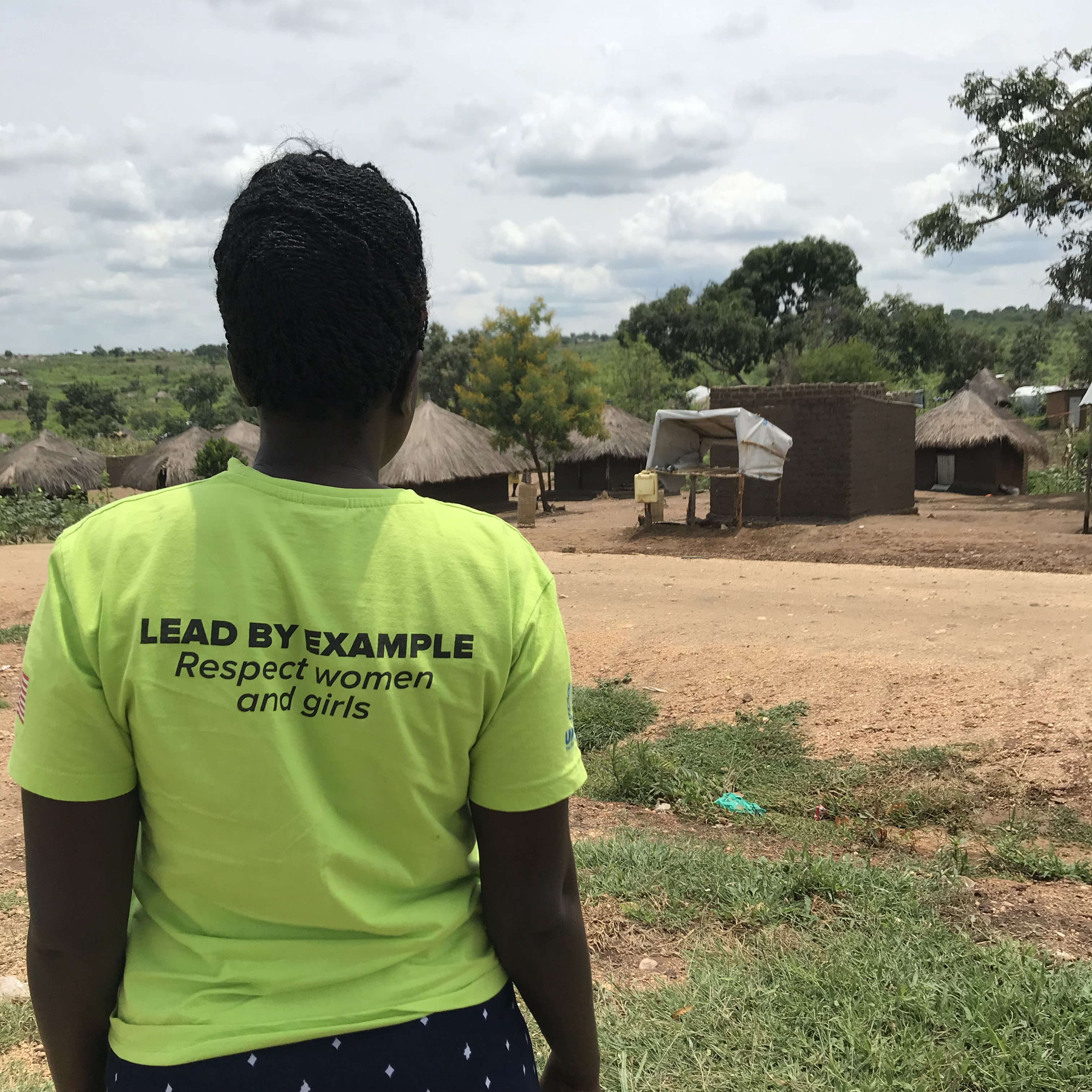 """A woman stands with her back to the camera. Her yellow shirt reads """"Lead by Example—Respect women and girls."""""""