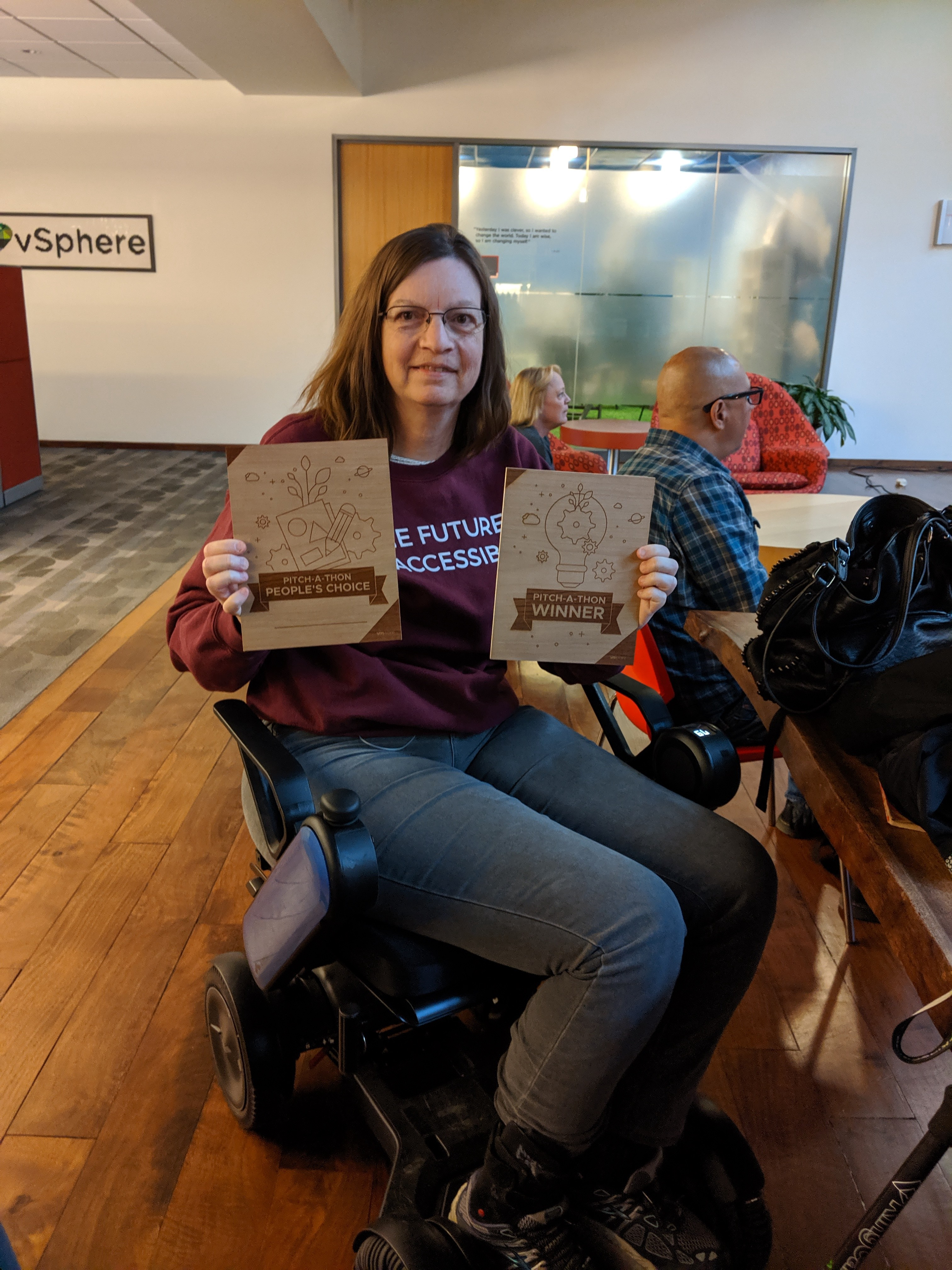Sheri, our Head of Accessibility, holding up two plaques she won for having the best pitch at a VMware Pitch-a-thon.