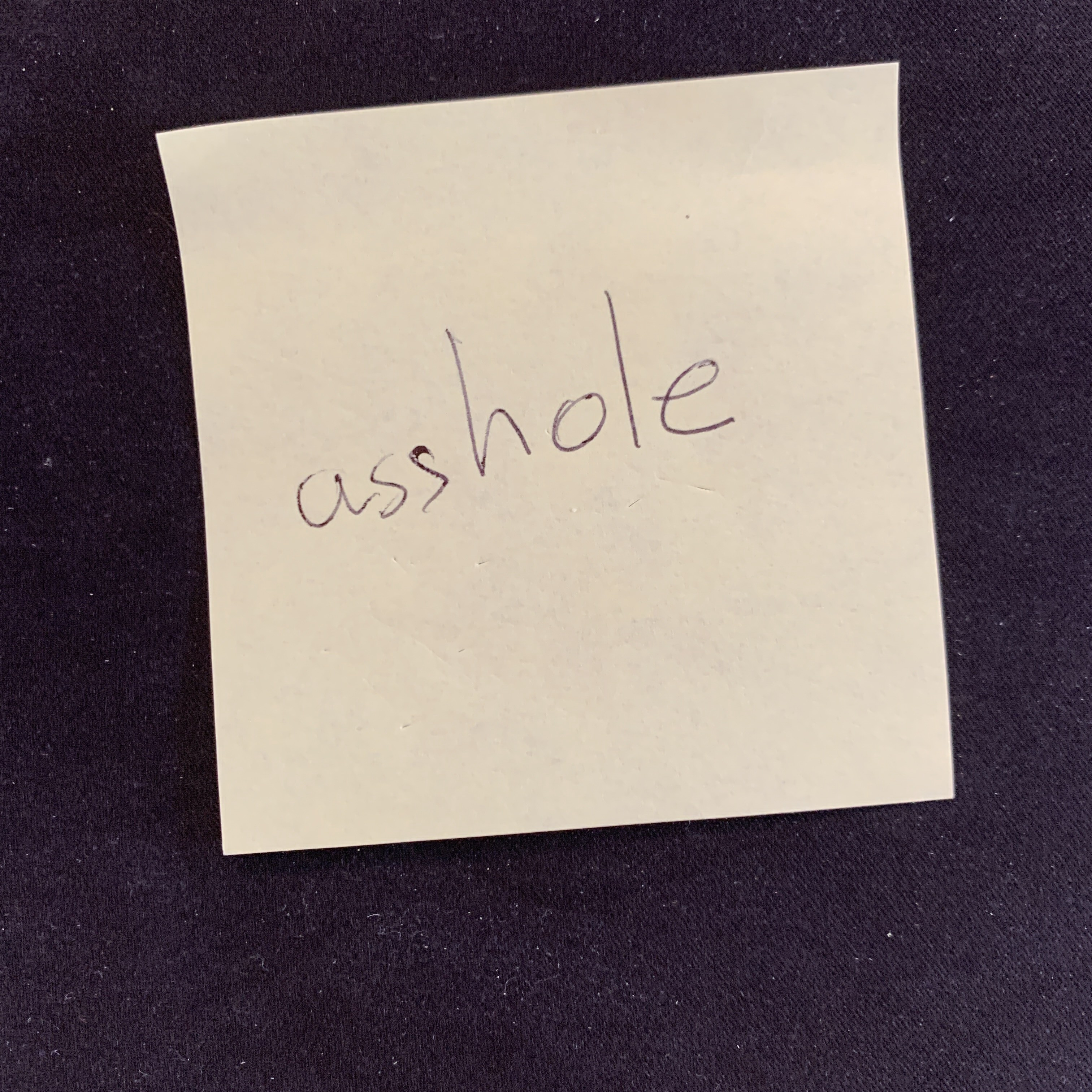 """Post-it note with word """"asshole"""" written on it"""