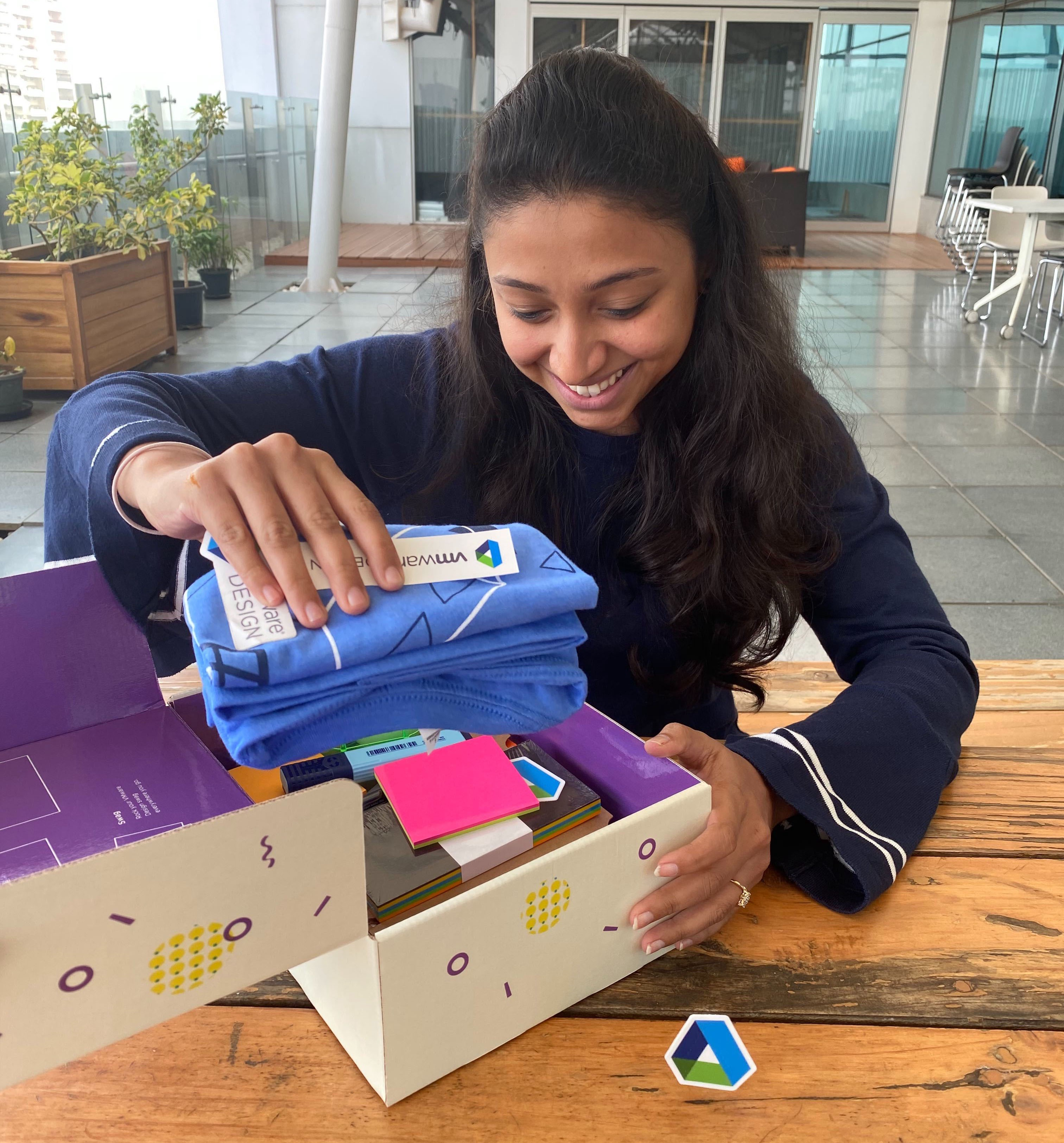Shibani, one of our newest hires, opening her welcome kit and taking out a VMware design t-shirt.