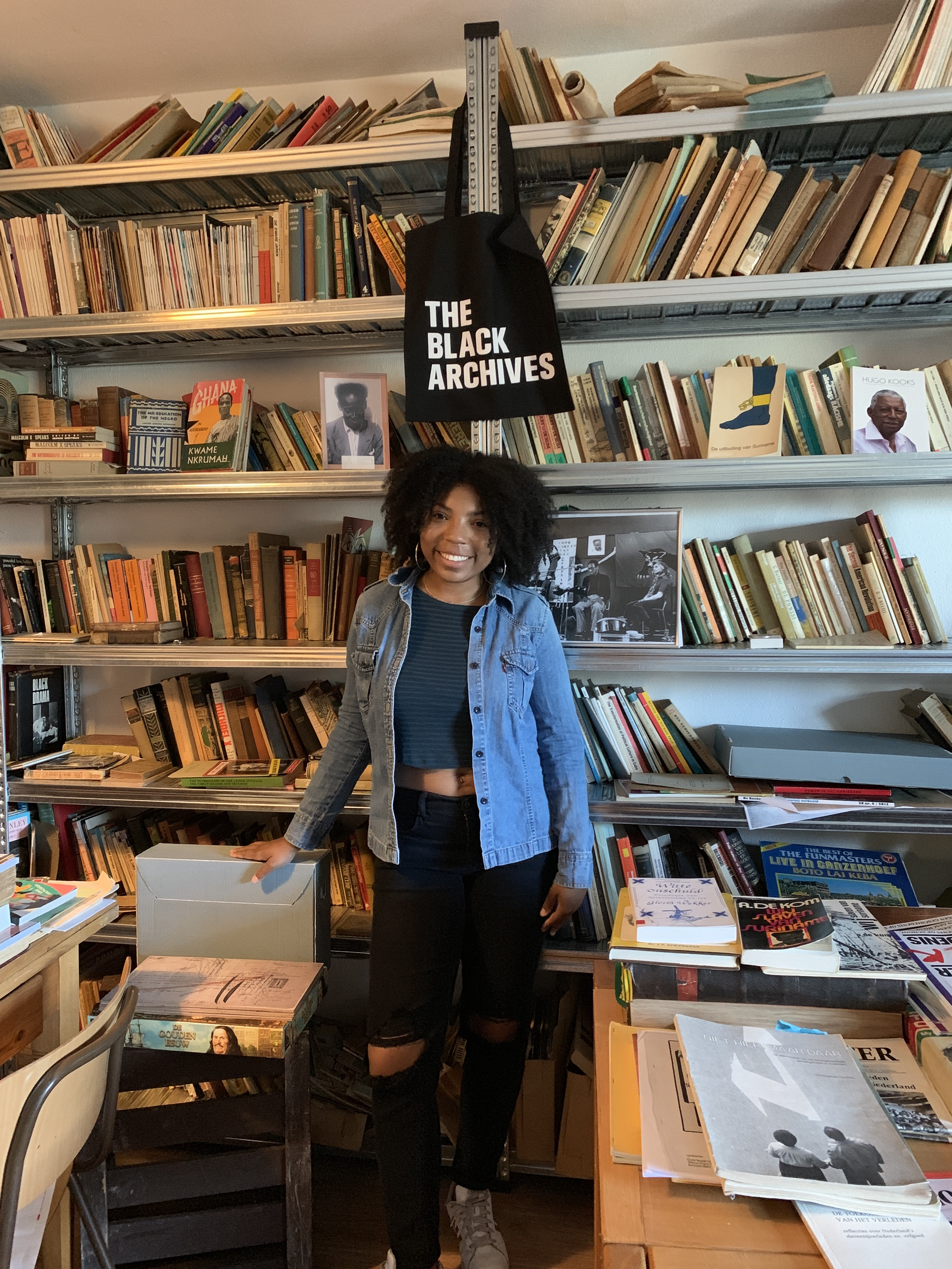 Kellan in front of two bookcases featuring Afro-Dutch people and a sign that says The Black Archives.