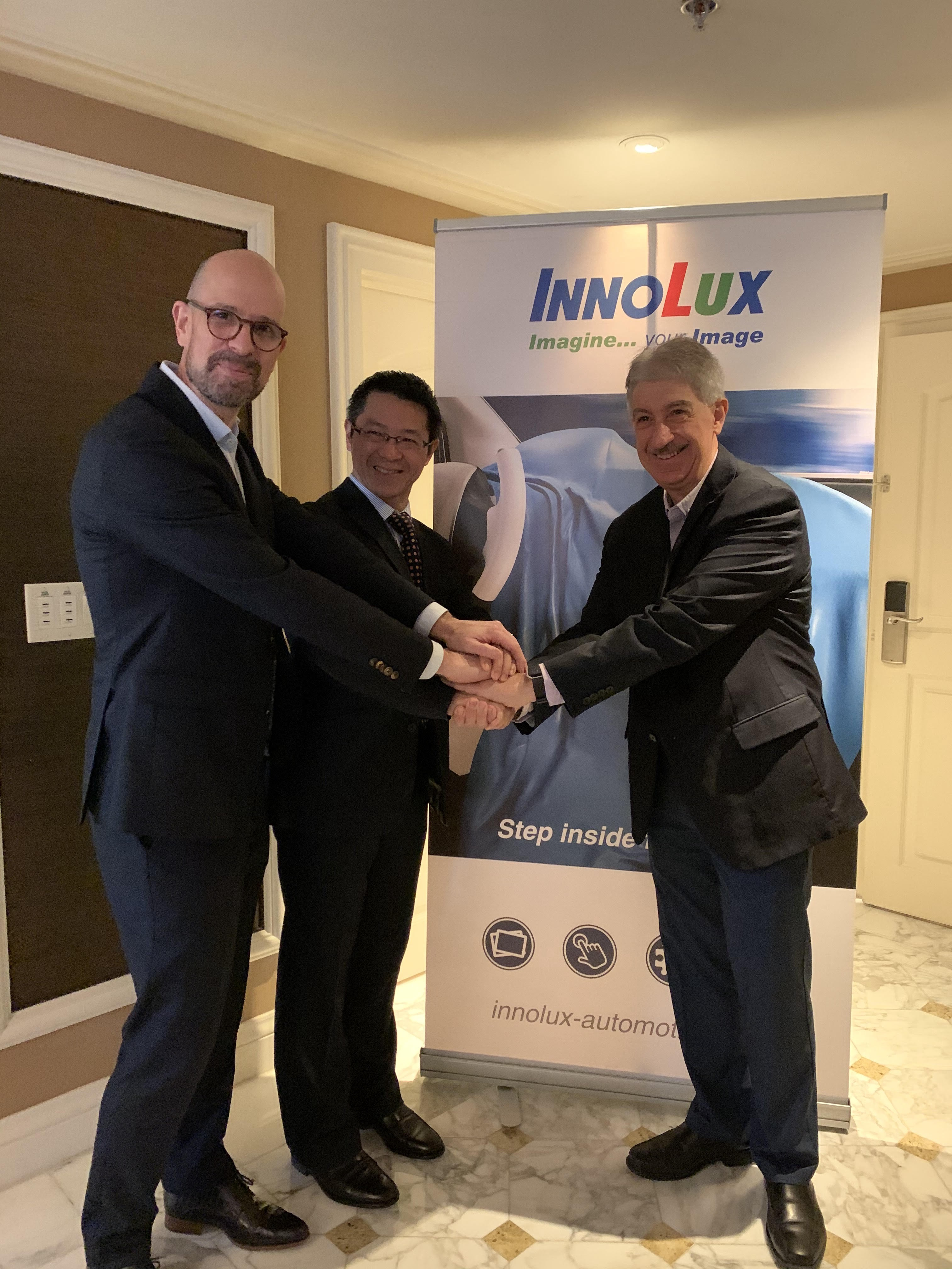 Innolux and Tanvas executives shaking hands in front of an Innolux banner stand