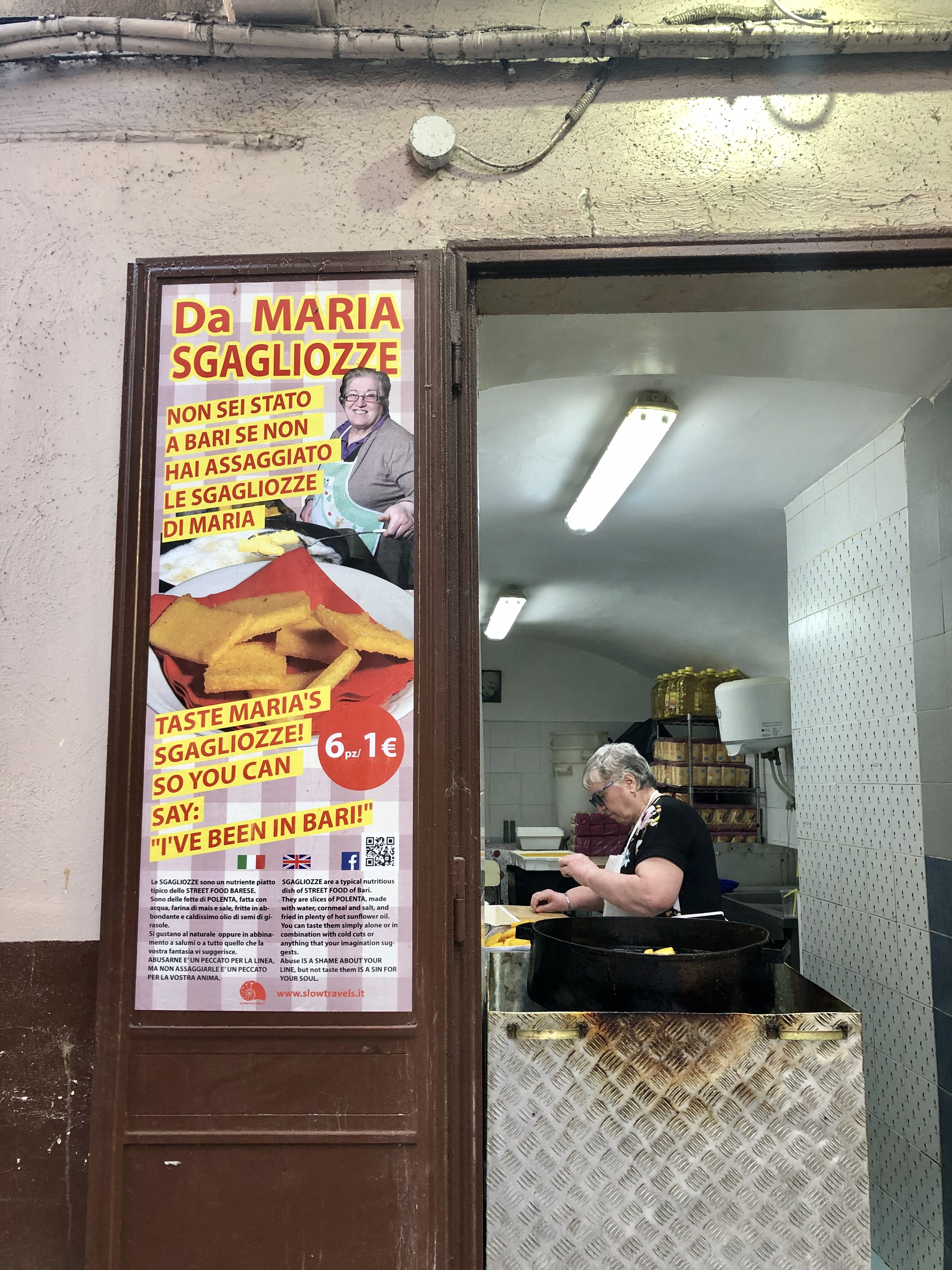 Maria working at the fryer next to a poster advertising her sgagliozze.