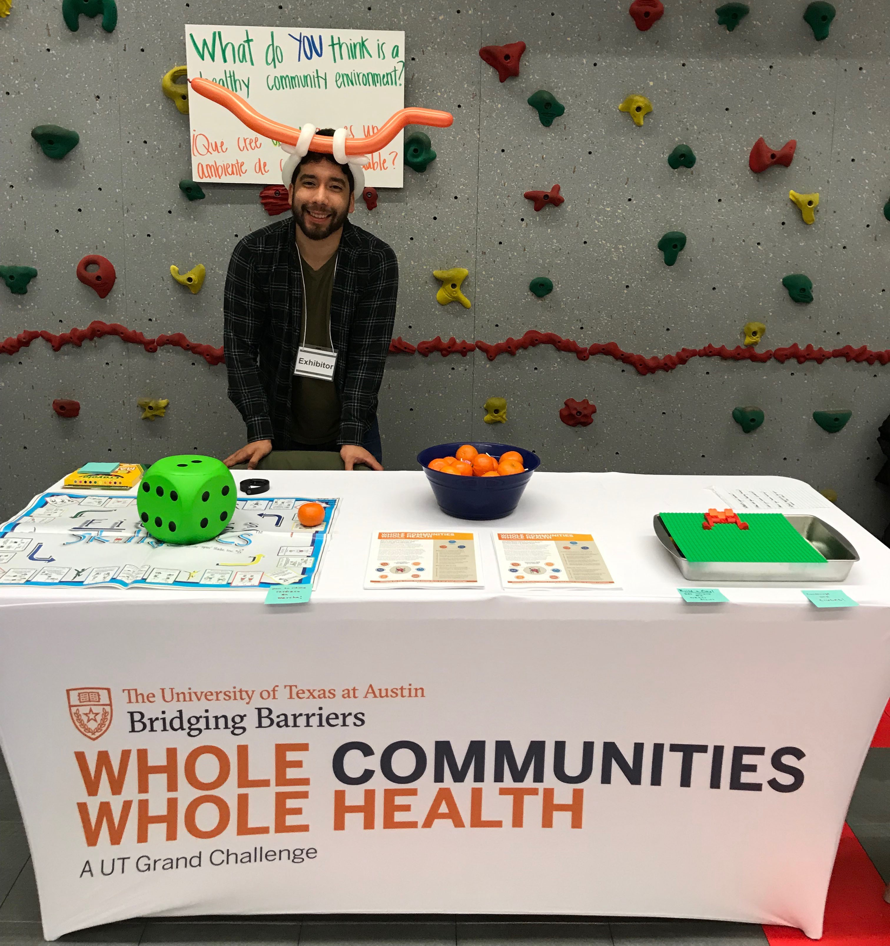 A UT Austin graduate student wears a longhorn hat and stands beside a Whole Communities–Whole Health table at an event.