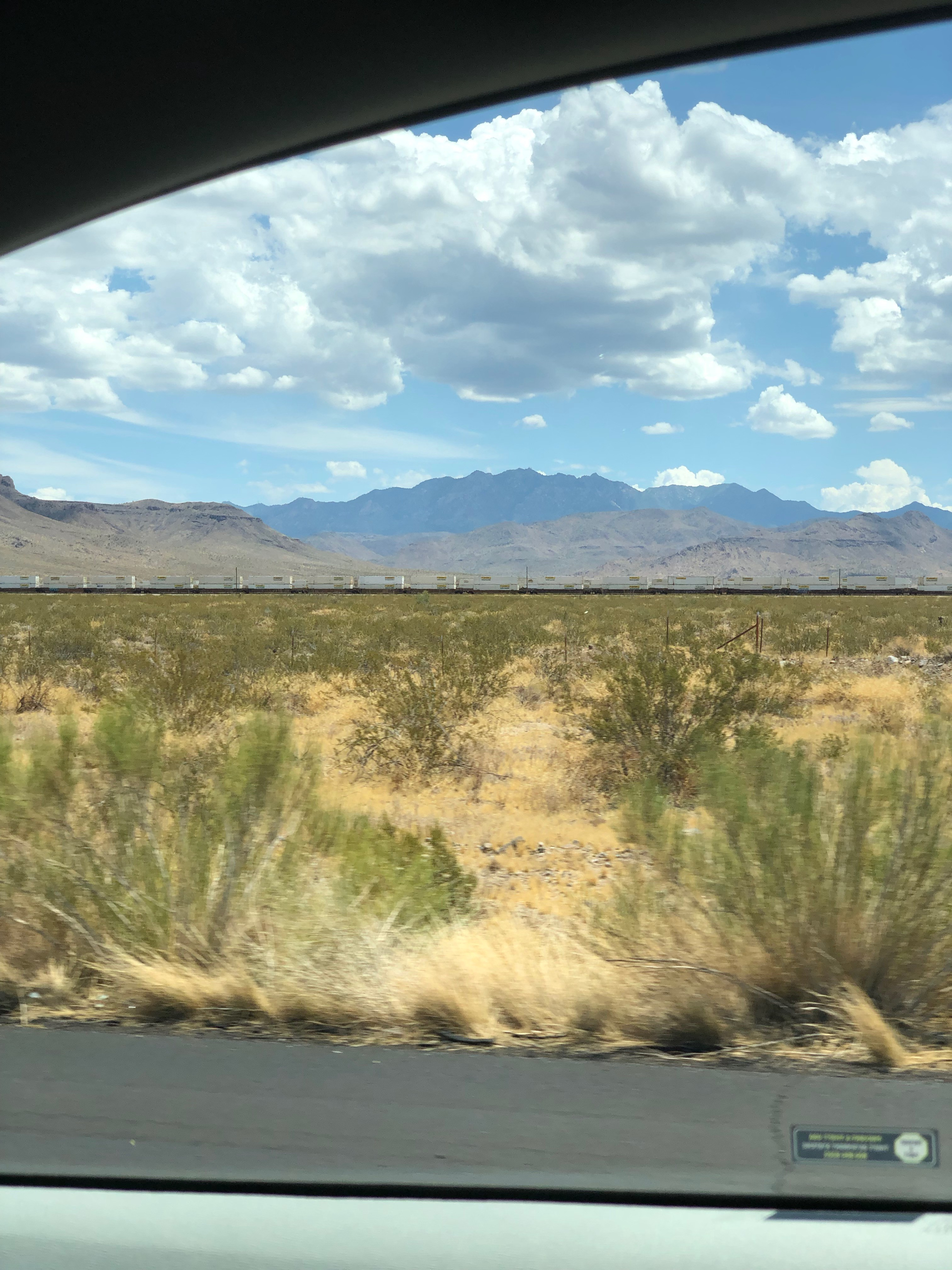 Picture of the Arizona desert and mountains taken through a car window.