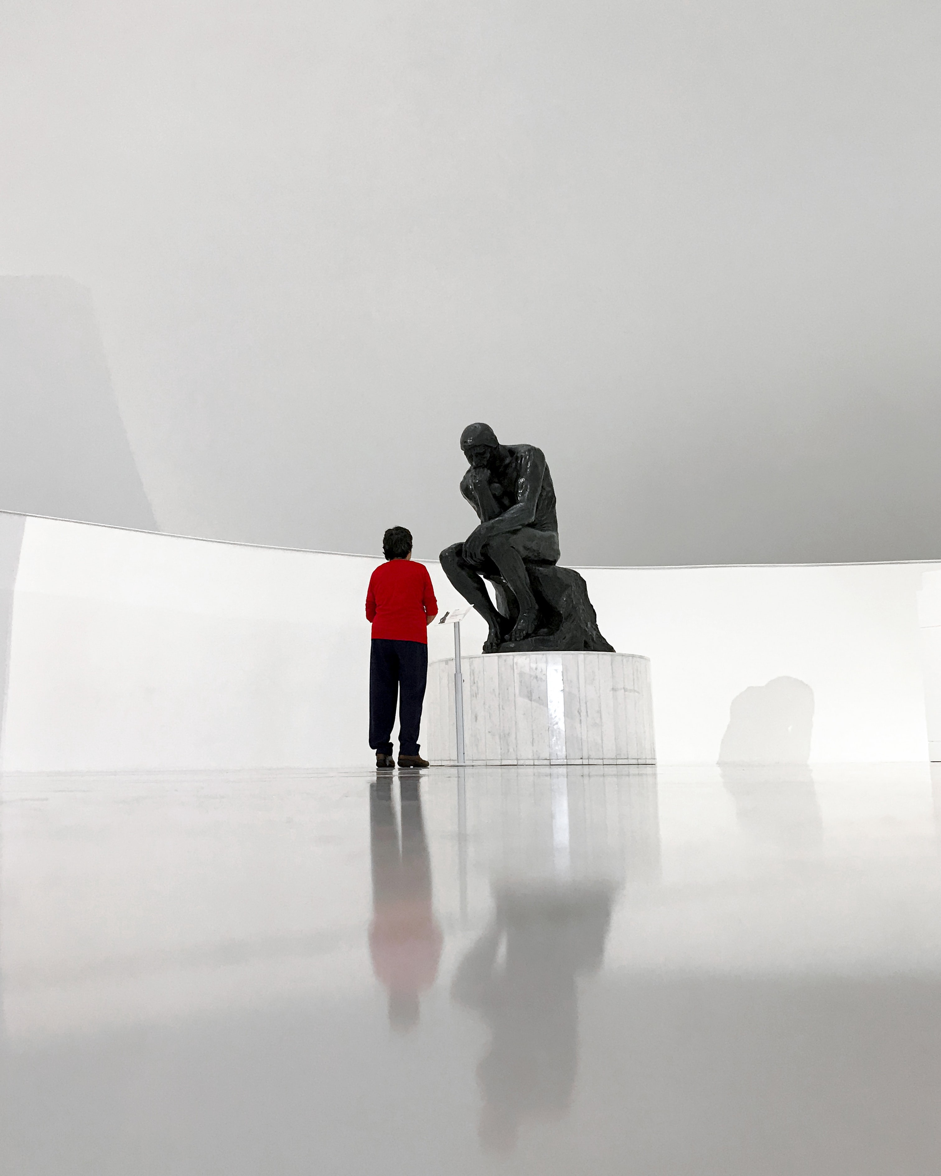 A person stands in front of the Thinker sculpture