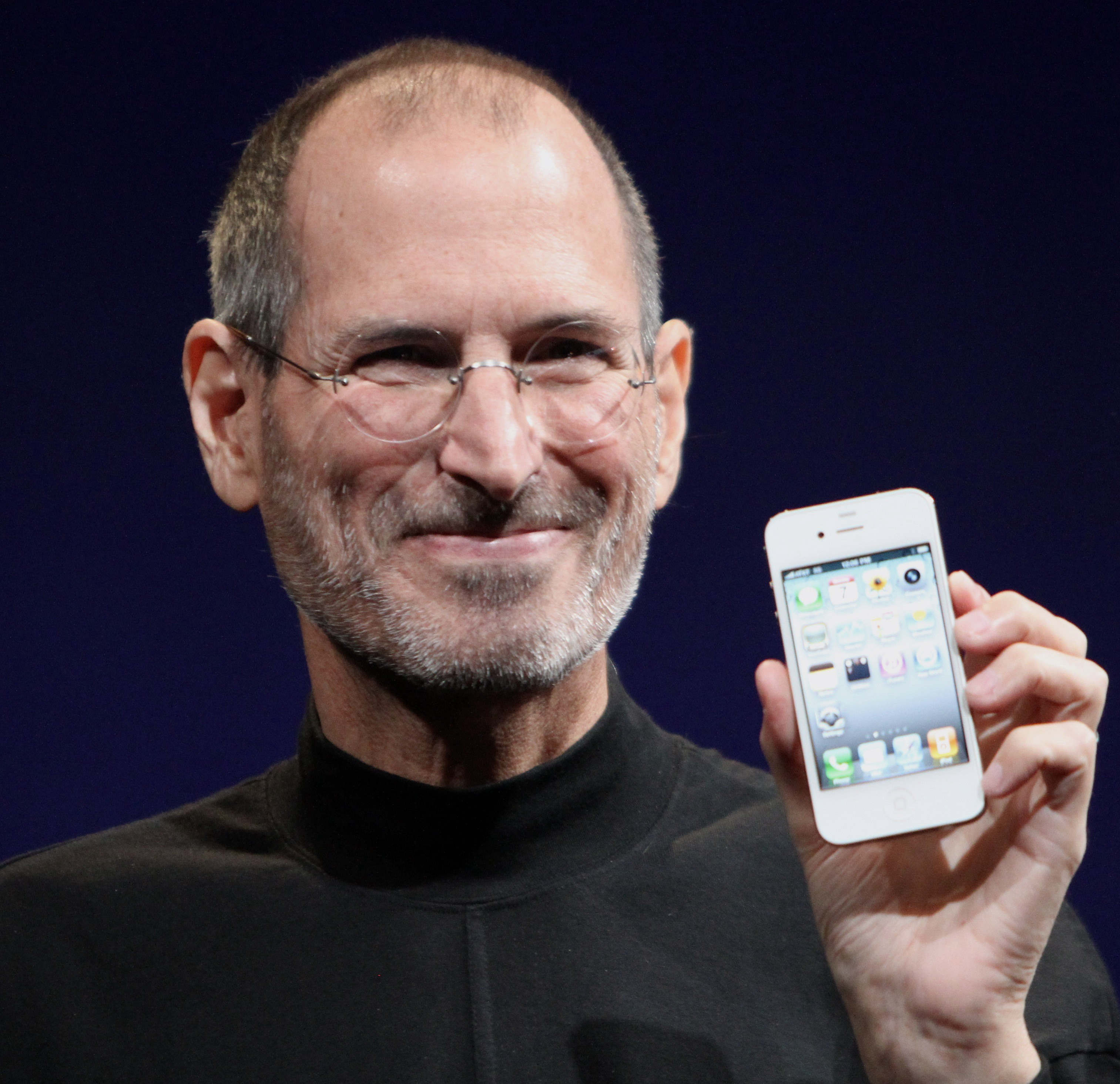The odd and unusual Steve Jobs holding an early iPhone in his hand.