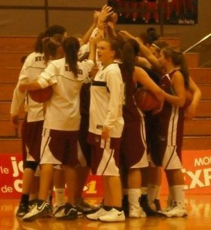 A group of women in a huddle on the basketball court, with their hands touching above their heads