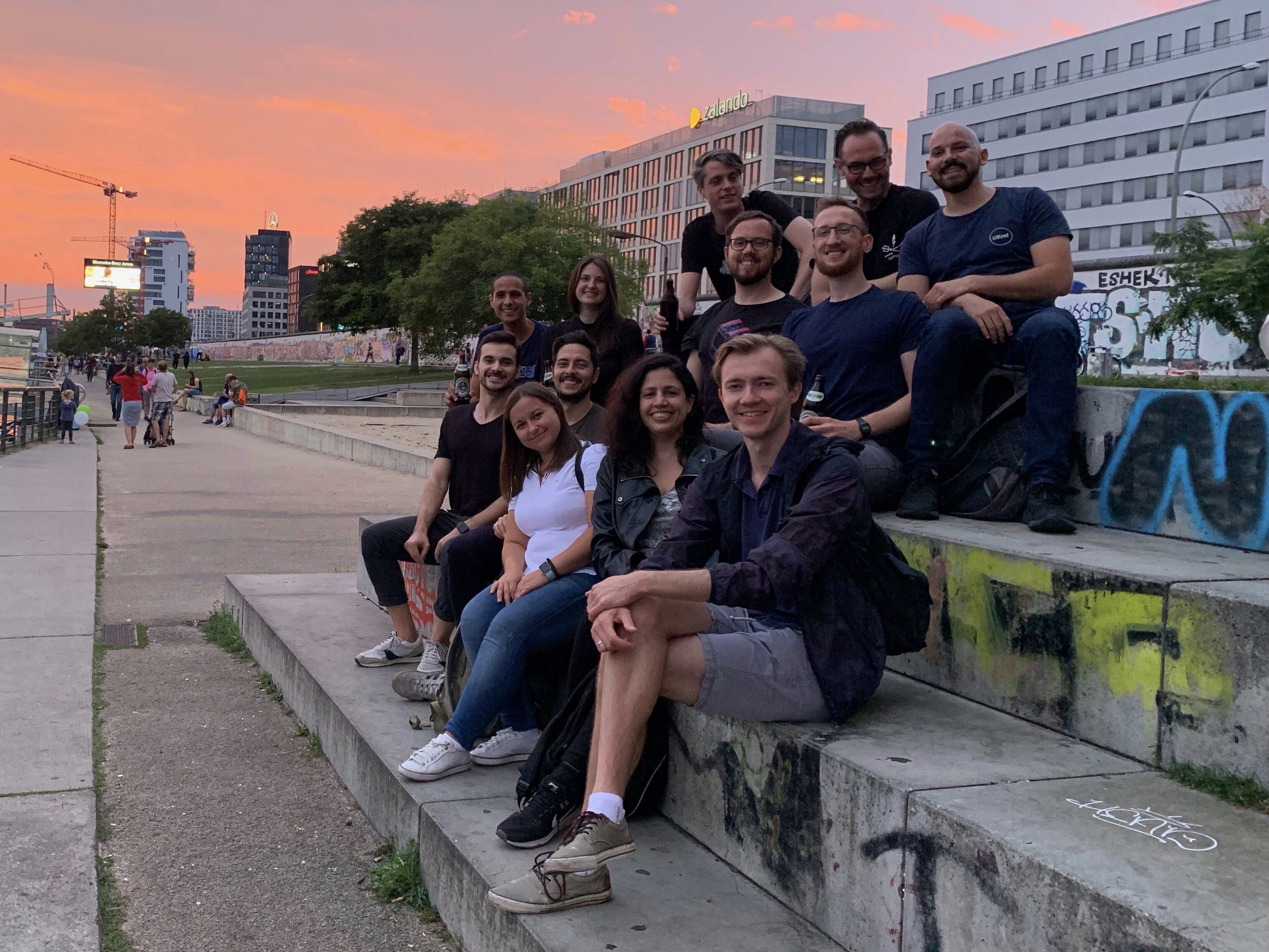 A photograph of 9 men and 3 women seated on concrete stairs in front a Berlin sunset