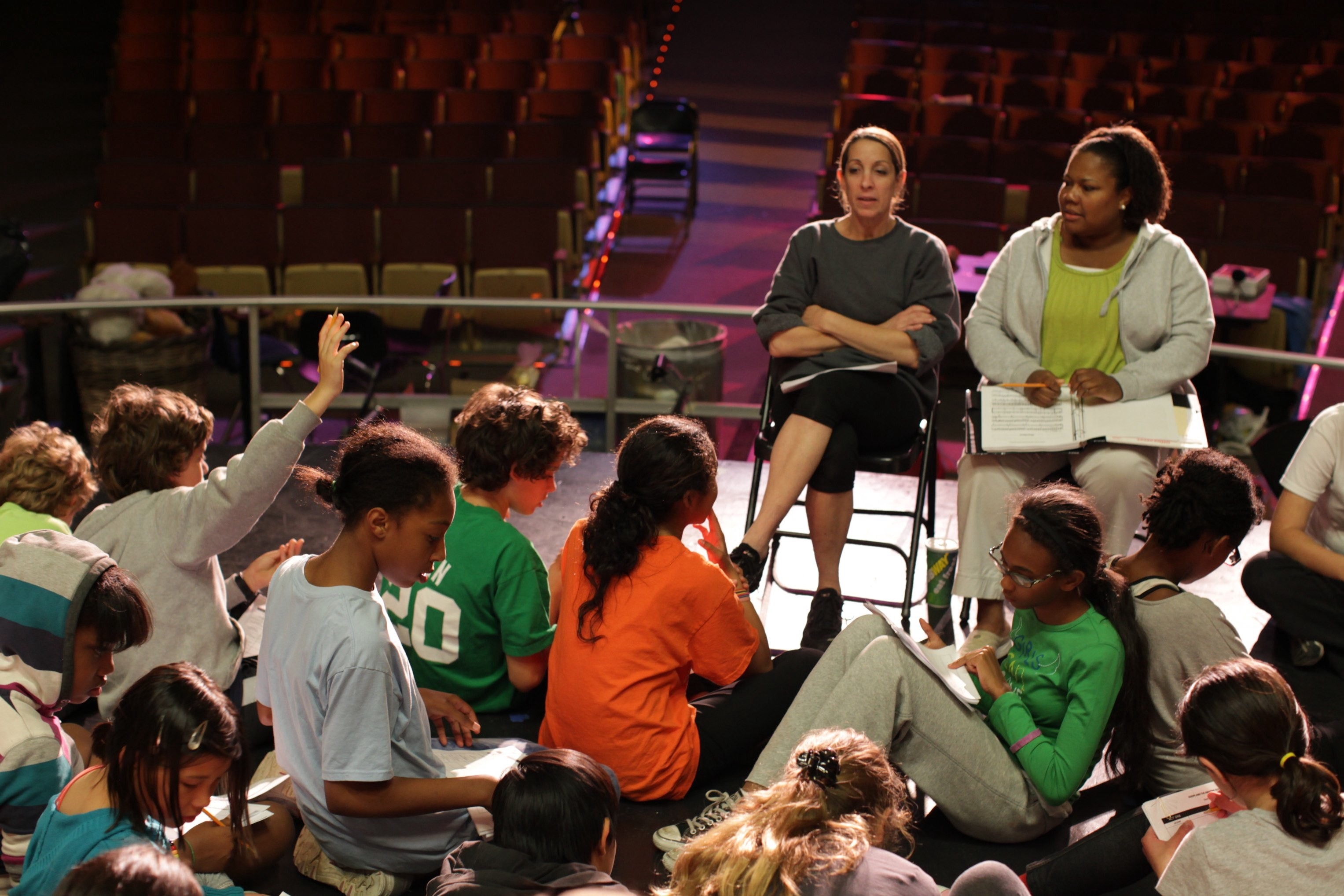 Diane R. Feldman ( seated on the left/dark grey sweatshirt) gives notes after a rehearsal