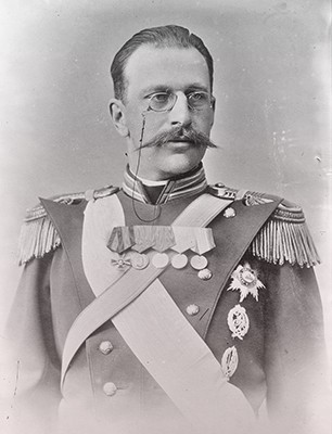 George in a military uniform covered with medals and orders. He has a pointed mustache.