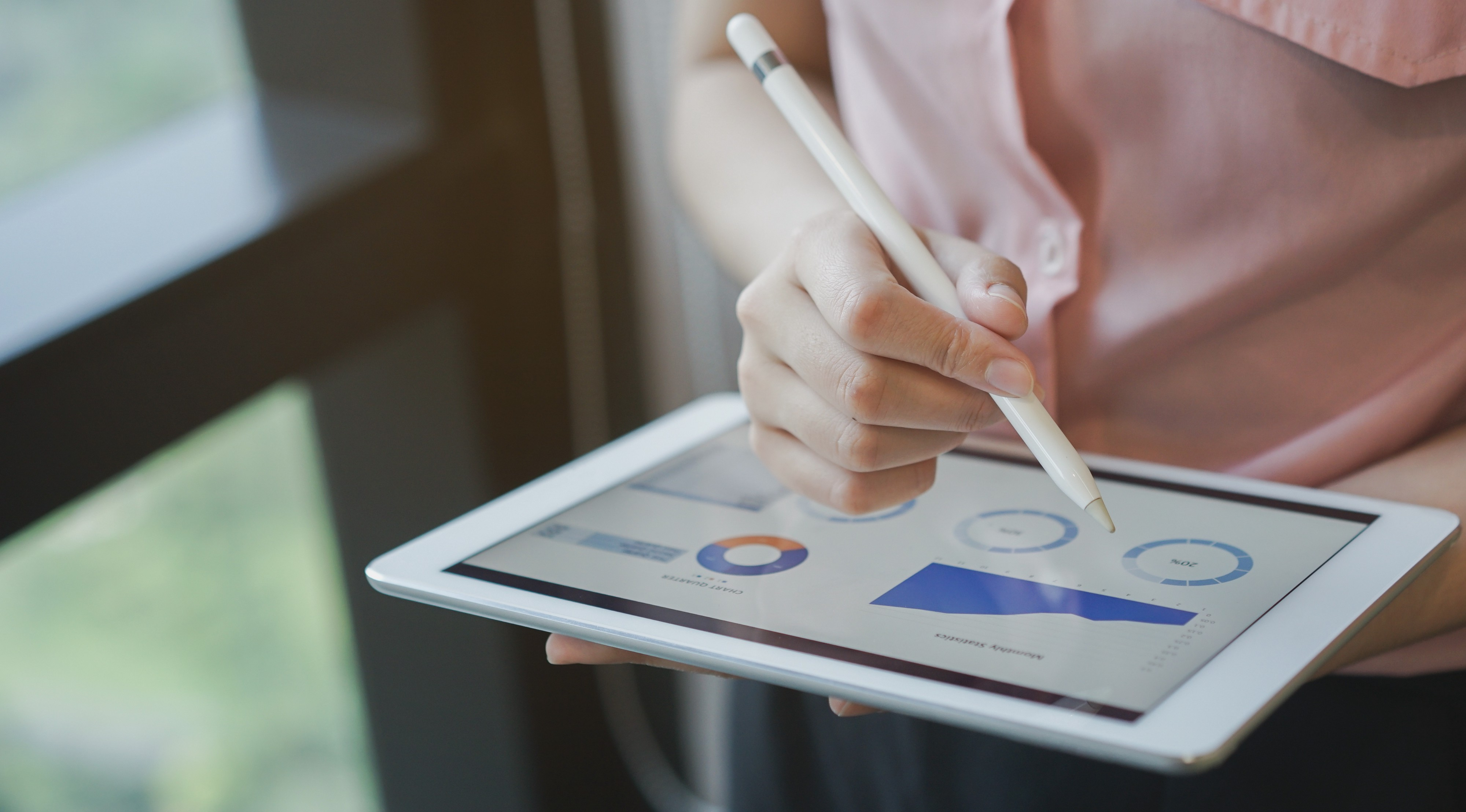 A close up on businesswoman's hand using a stylus pen on a tablet, commenting on a metrics dashboard.