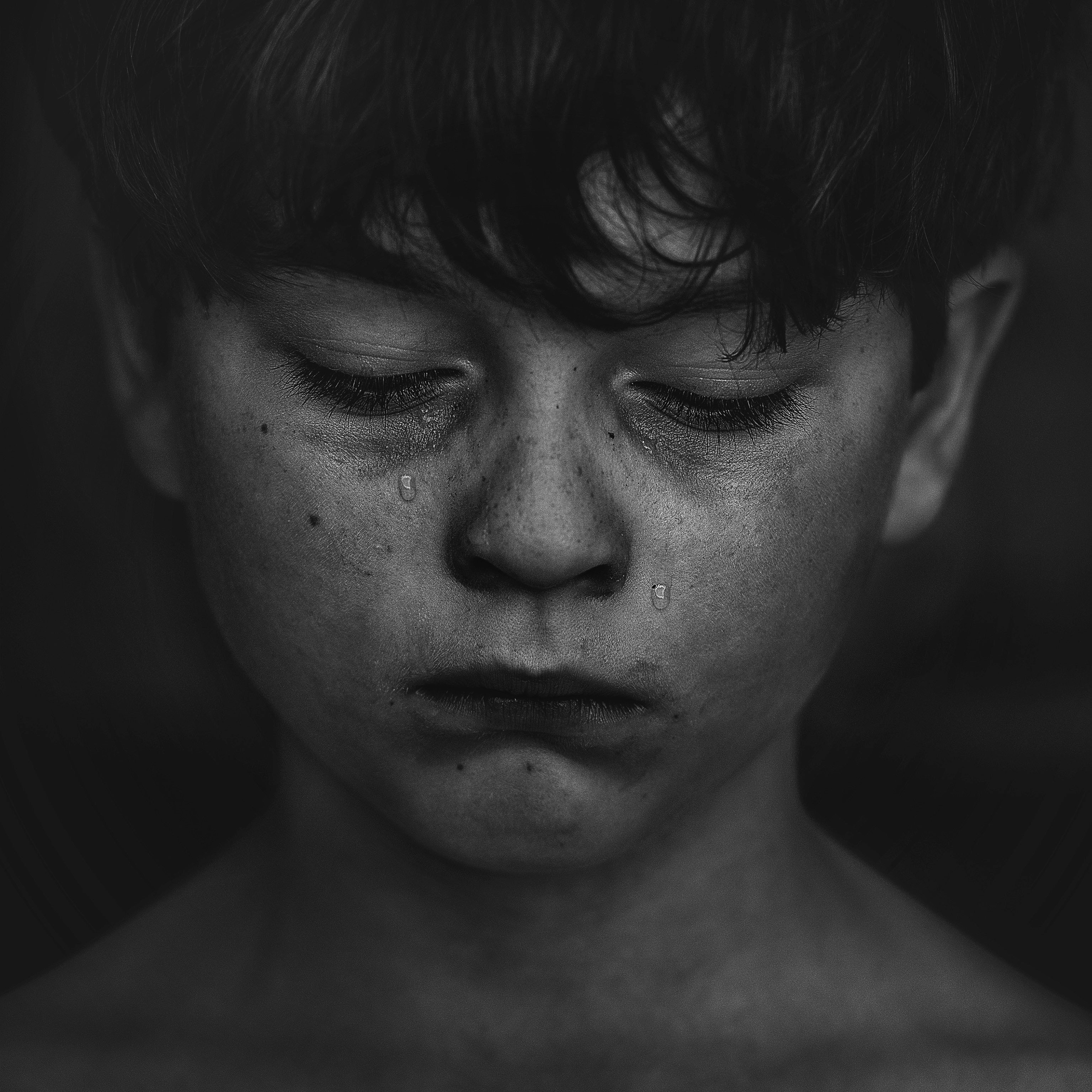 Grayscale photo of boy crying