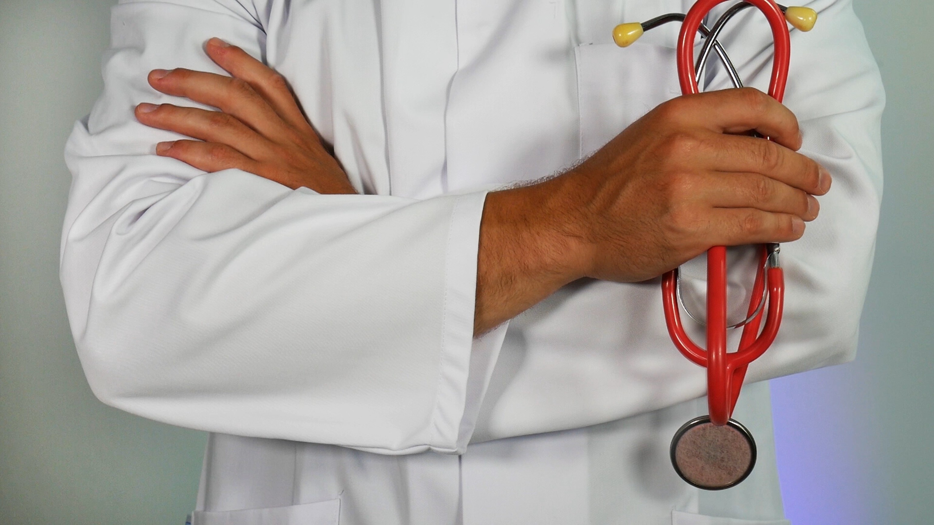 cropped photo showing the chest and arms of a man in a white coat who is holding a stethoscope with his arms crossed.