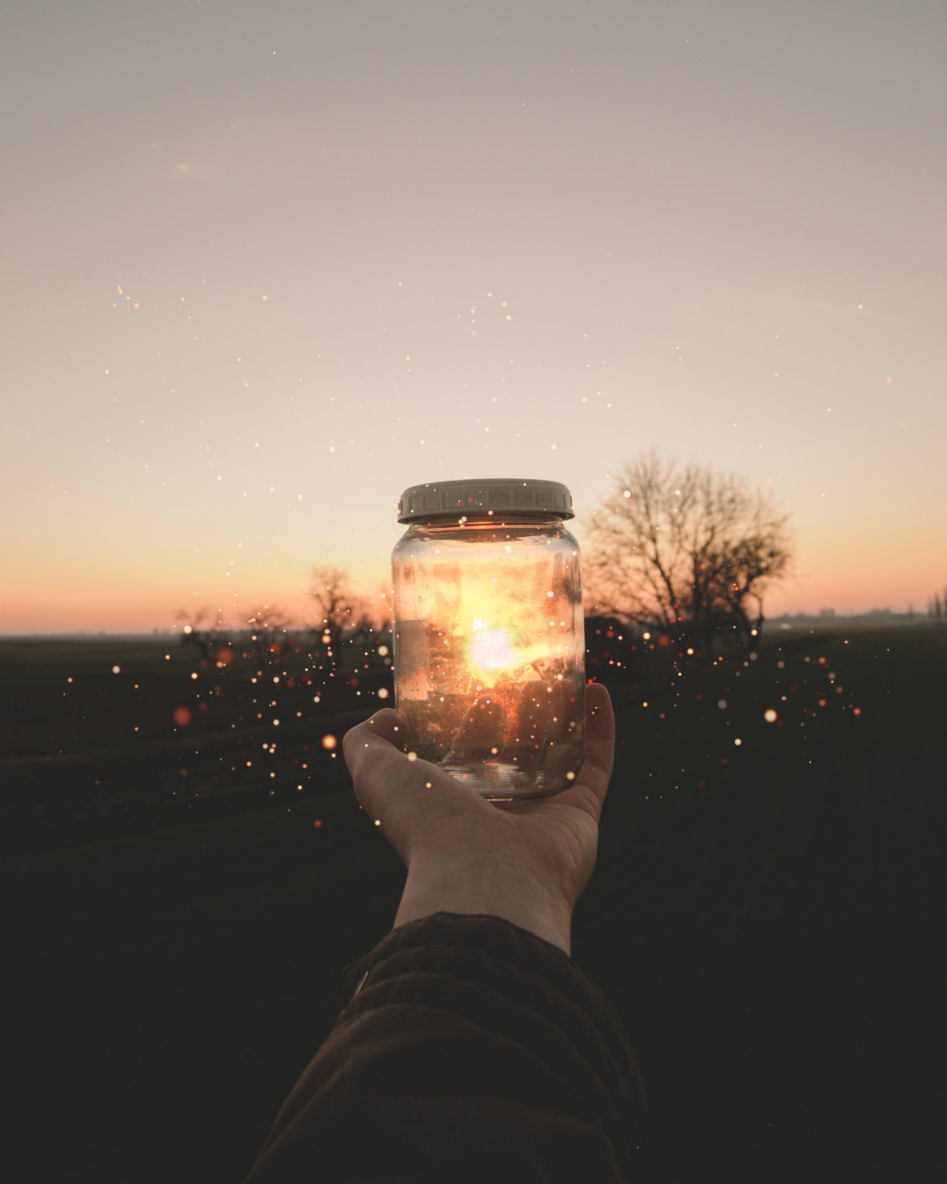 Ain image of a sunset obscured by a glass jar, creating a sparkling light effect.