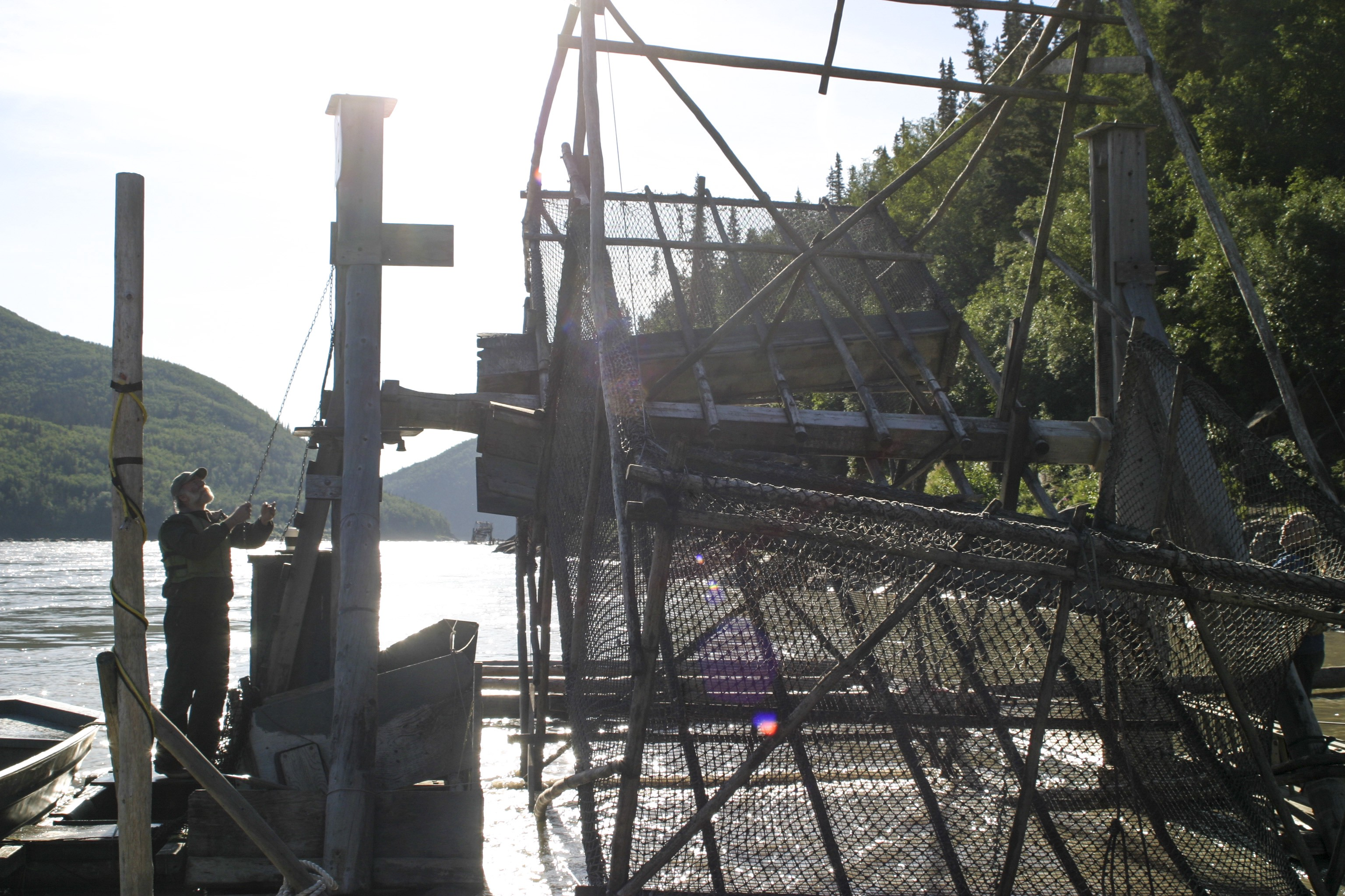 a man standing next to a large fish wheel in a river