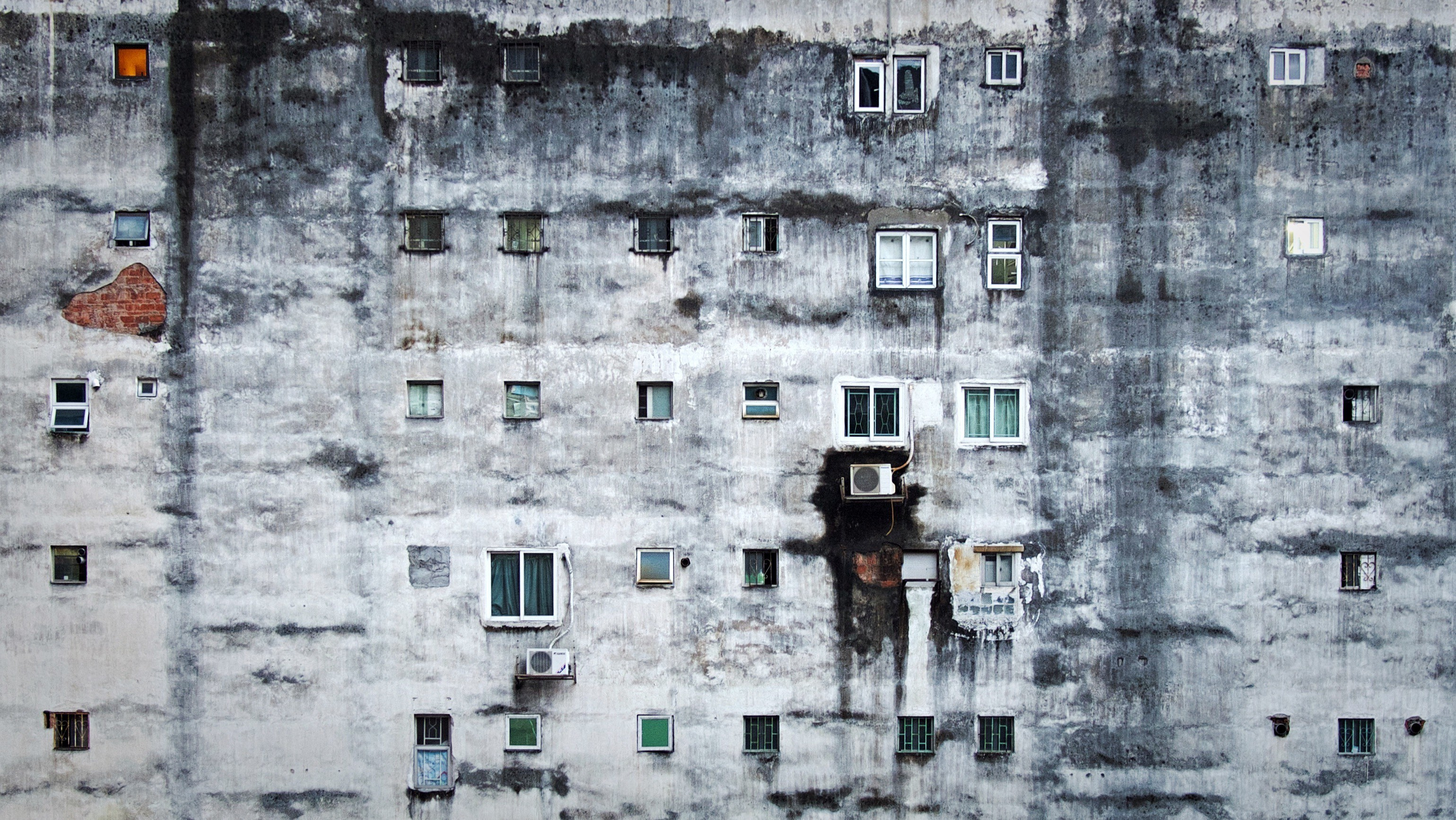 A dirty white wall six stories high which is the side of a run-down apartment building.