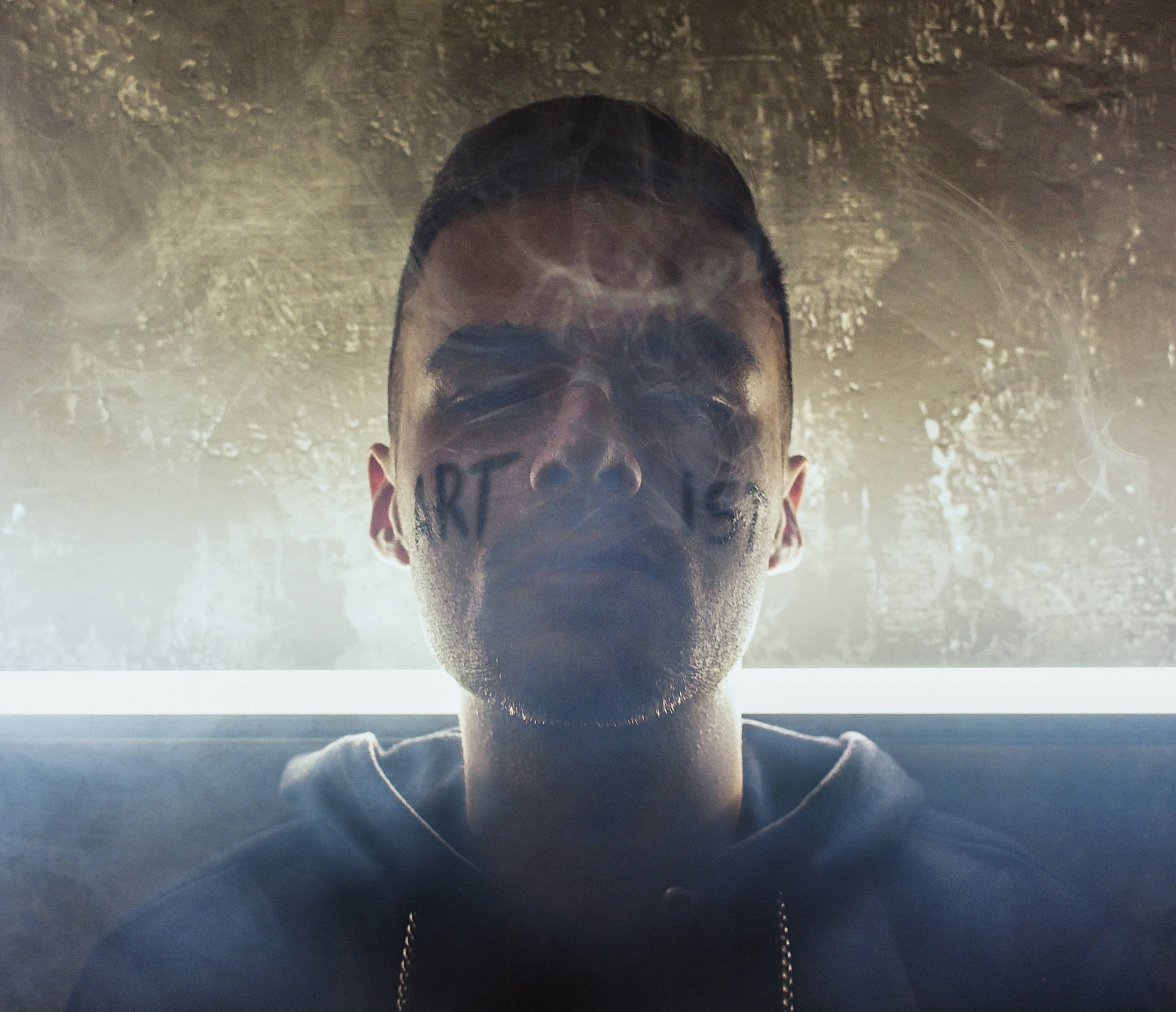 photo of a person with ARTIST written on his face